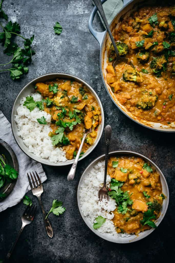overhead of two bowls of vegan pumpkin curry with jasmine rice