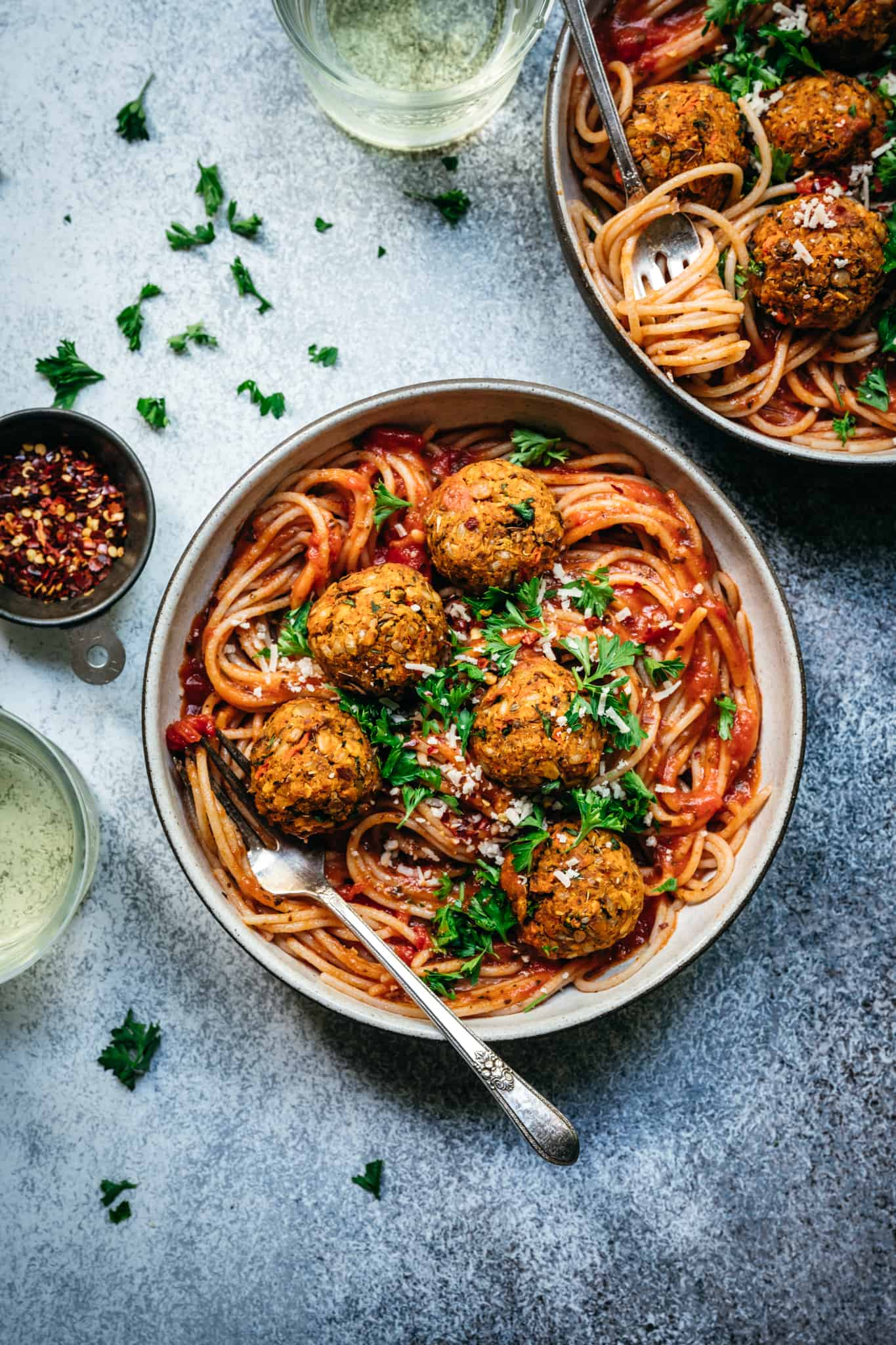 overhead of vegan lentil meatballs in red sauce with spaghetti in a bowl