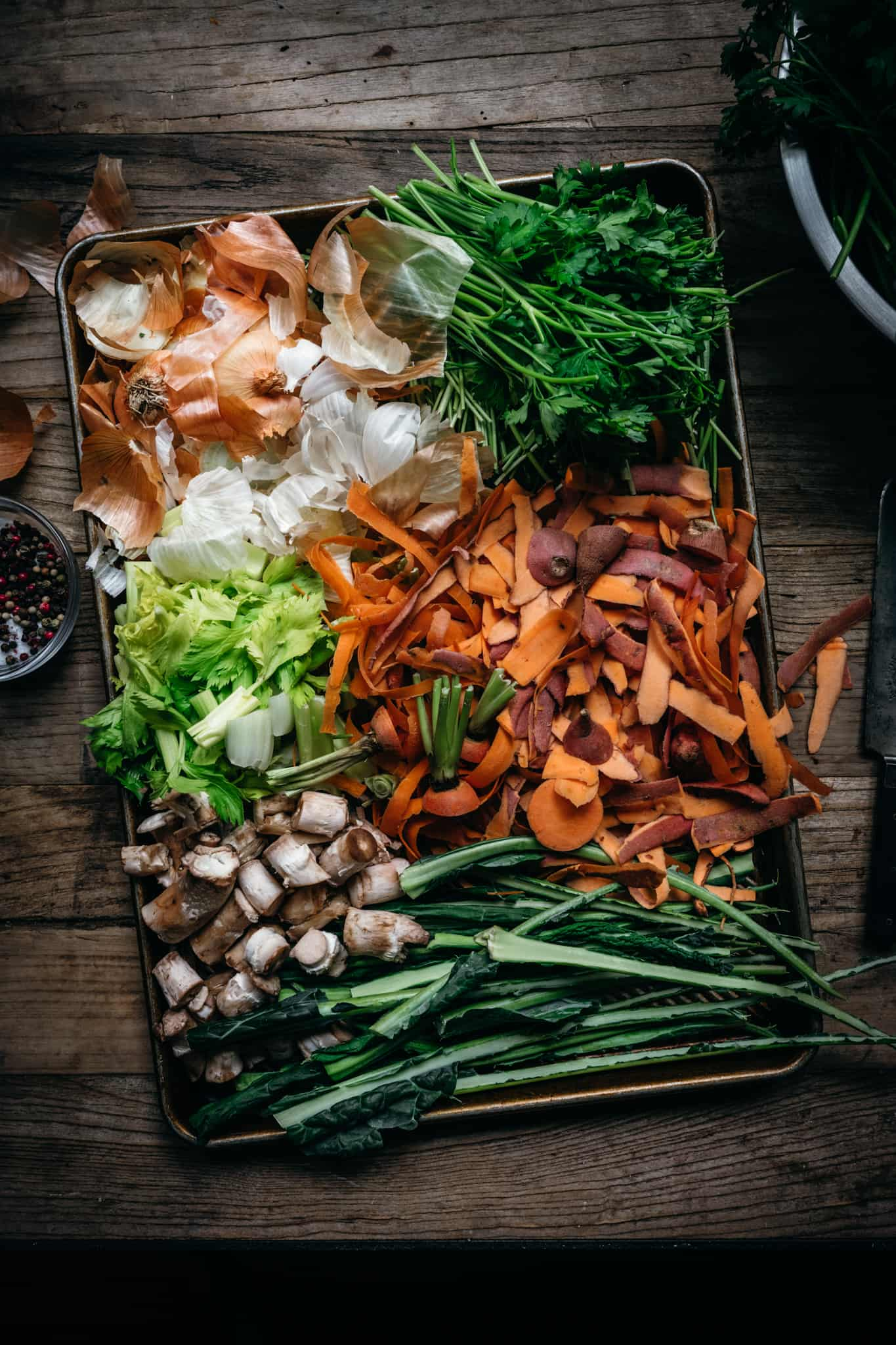 overhead view of vegetable scraps on sheet pan to make vegetable broth