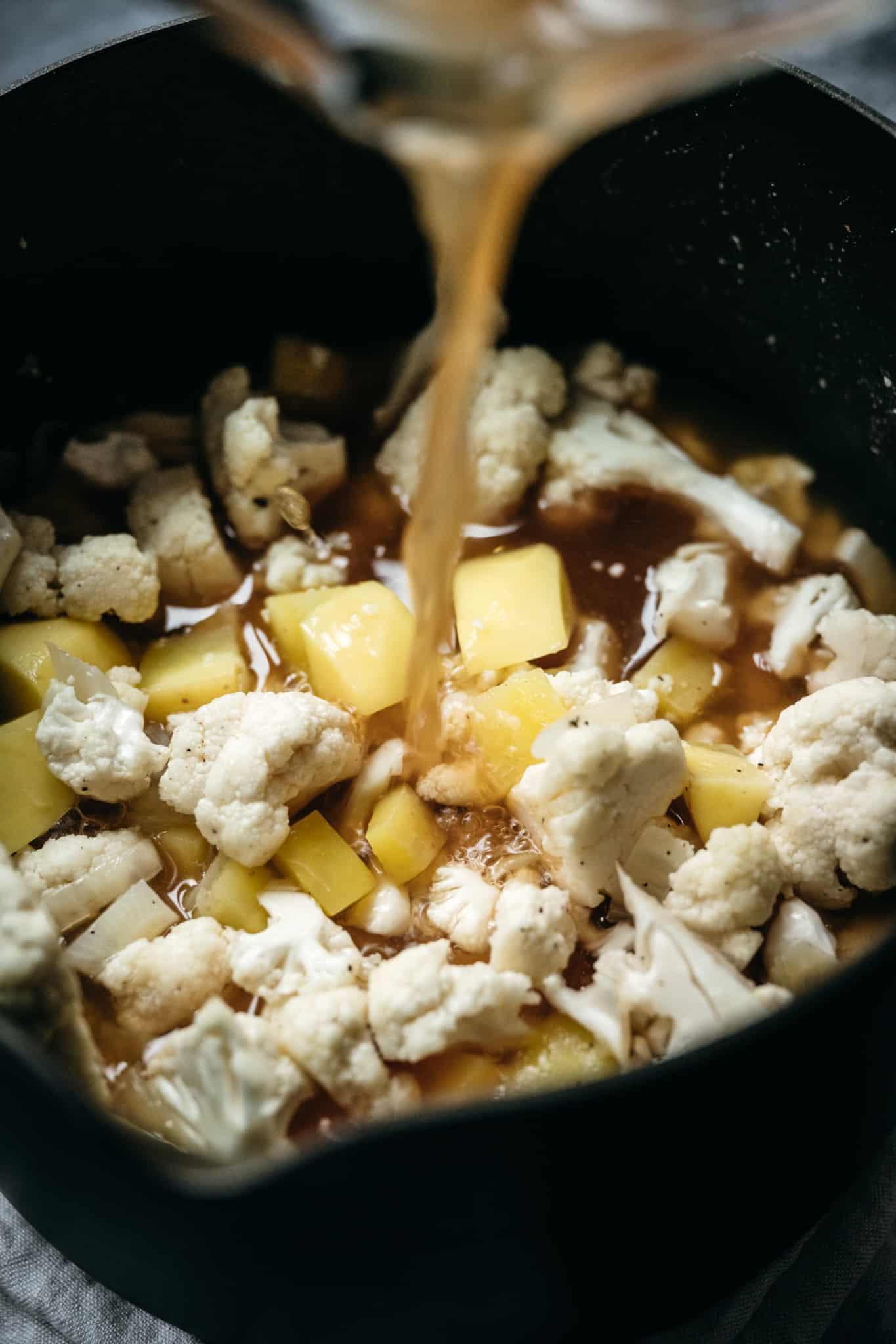 Pouring vegetable broth into cauliflower potato soup