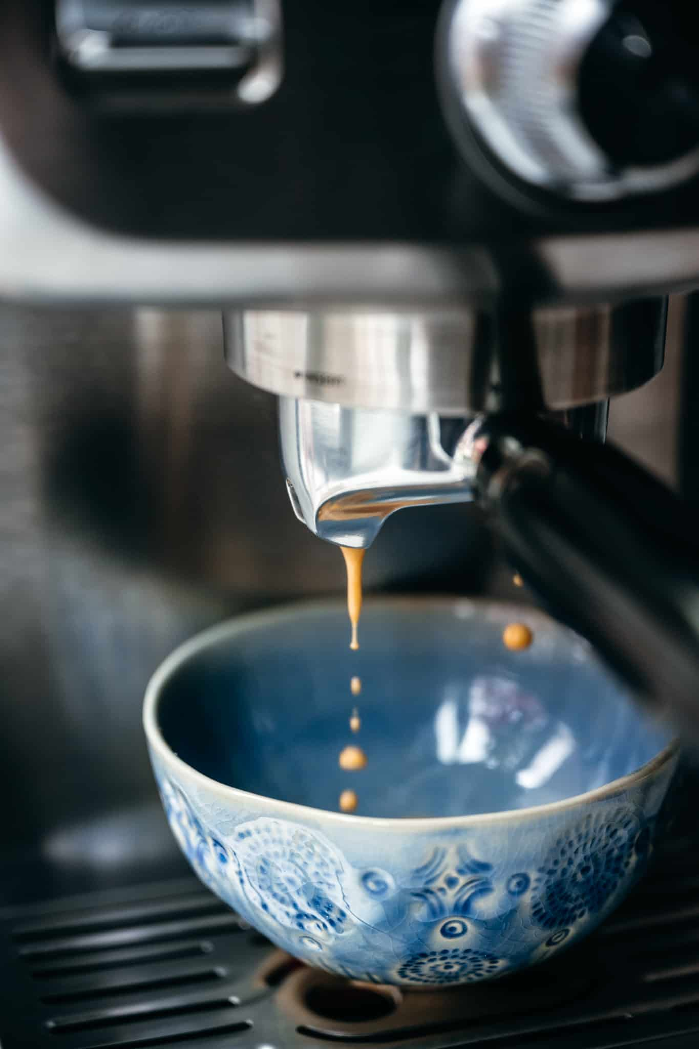 Espresso falling into blue coffee cup from machine