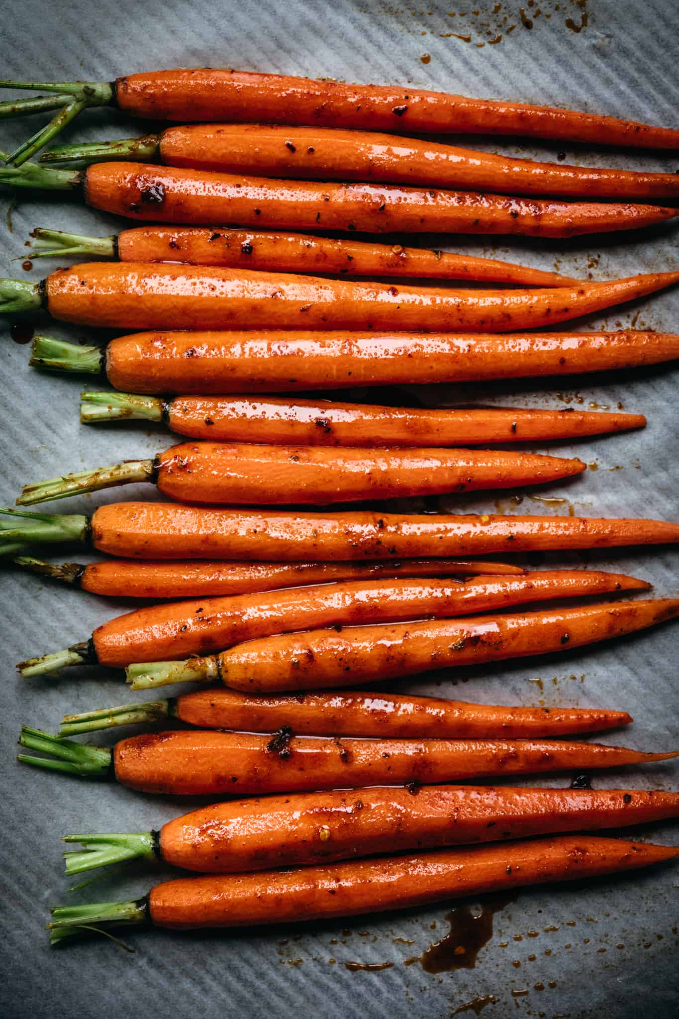 overhead of roasted carrots lined up on a metal baking sheet