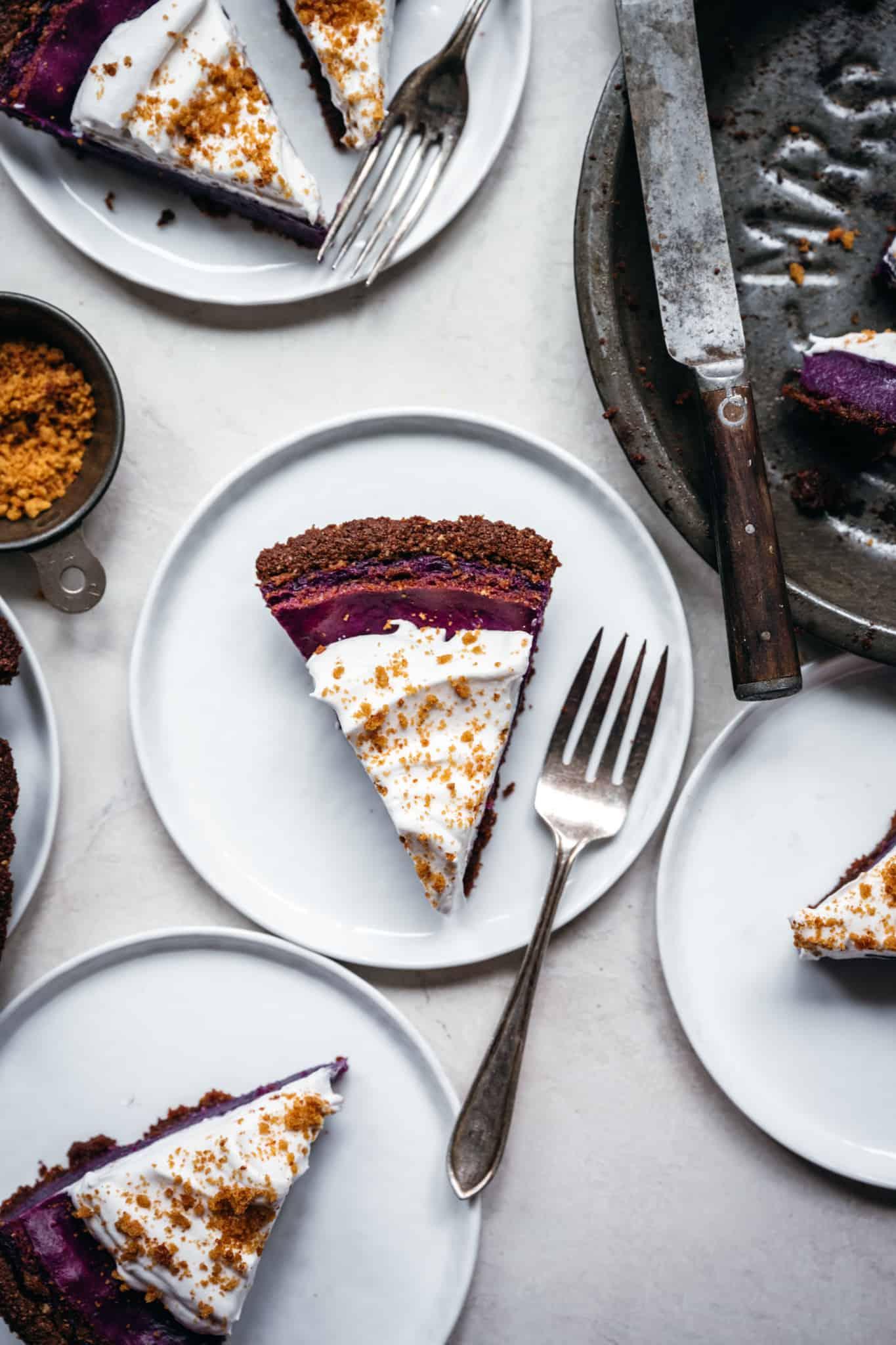 overhead view of slices of vegan purple sweet potato pie on white plates