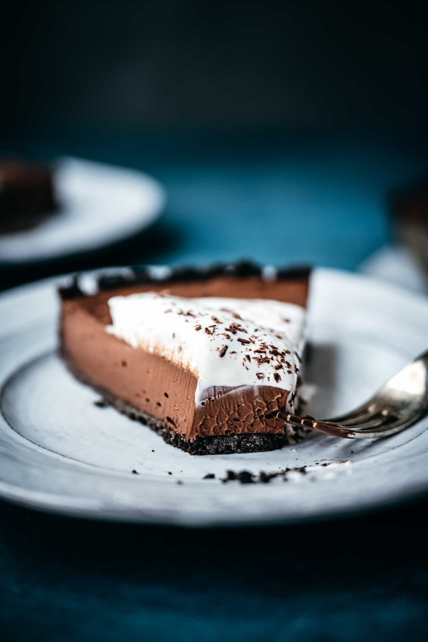 close up side view of texture of vegan chocolate cream pie on white plate