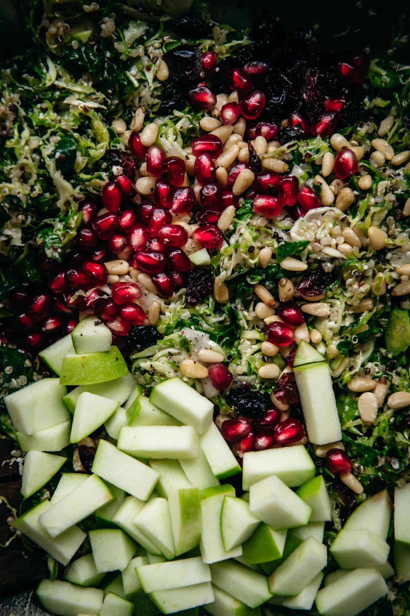 close up of shaved brussels sprouts salad before it's mixed with apples, cranberries, and pomegranate seedds