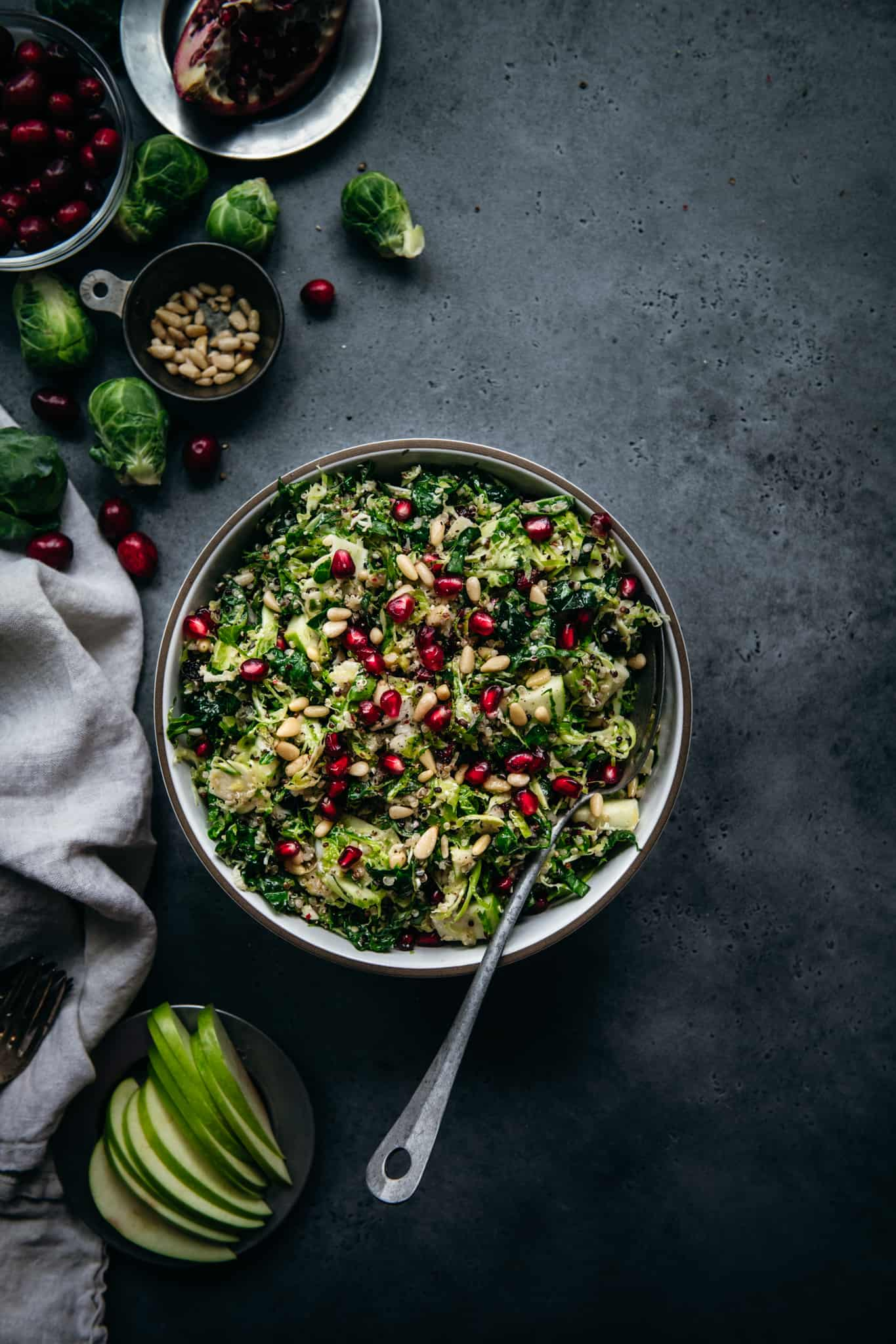 overhead of a bowl of shaved brussels sprout kale salad on a dark background