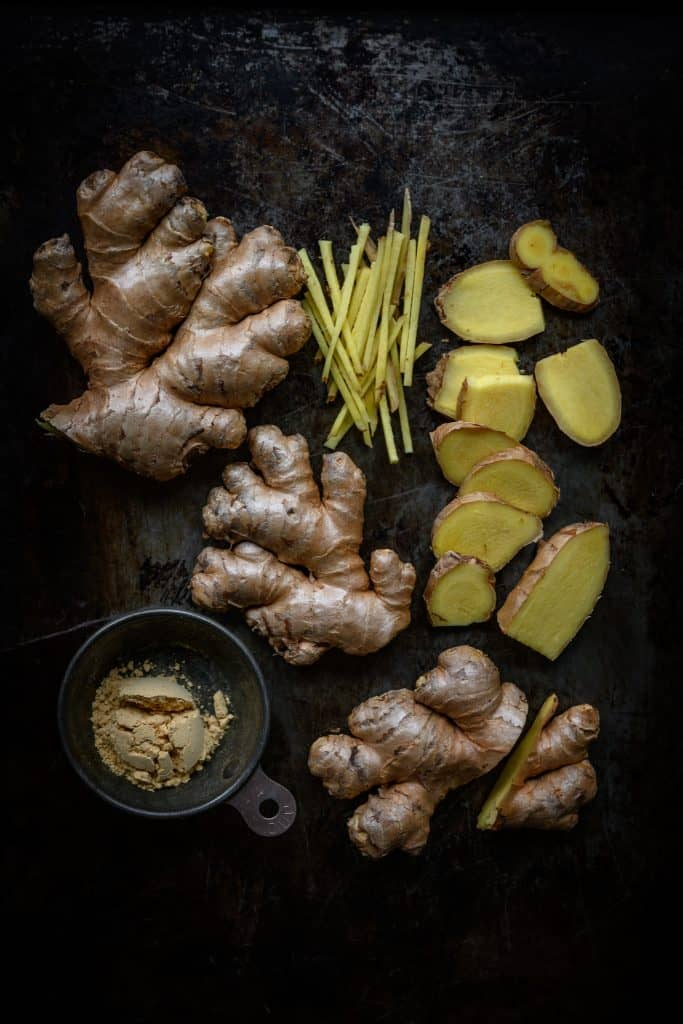 fresh and powdered ginger styled on a rustic dark background