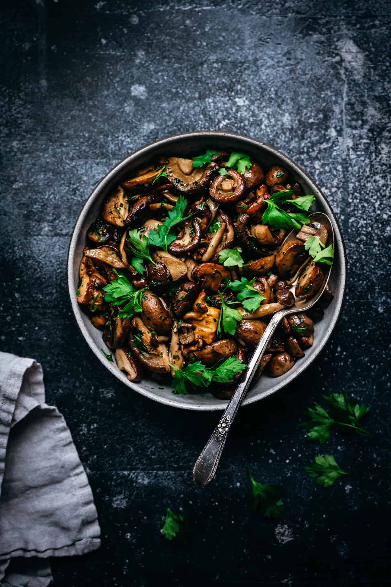 overhead of pan roasted wild mushrooms in a bowl with a spoon