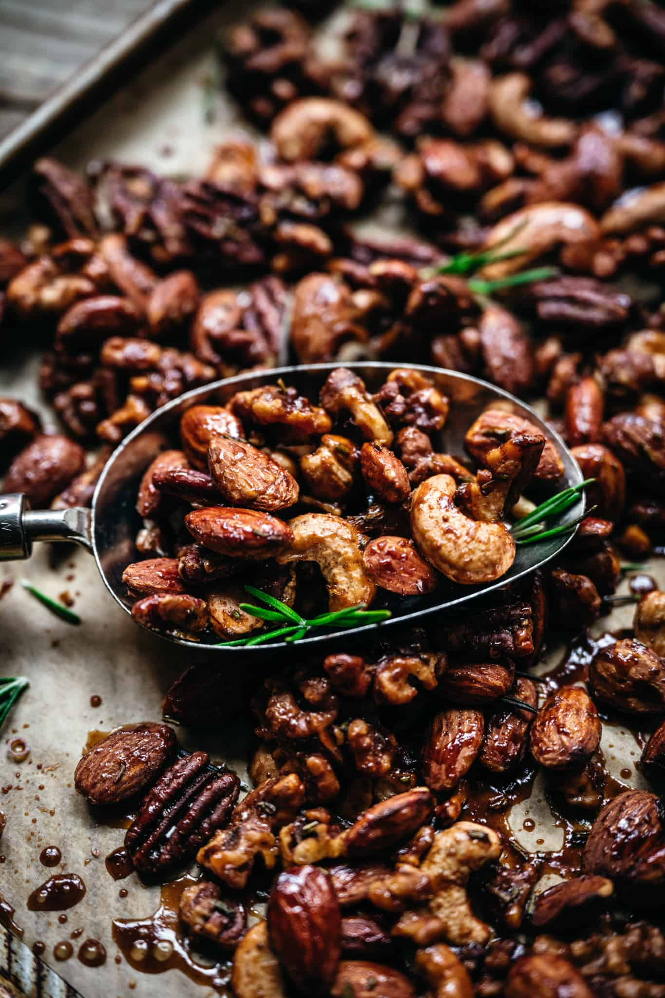 close up of mixed spiced nuts on a baking sheet with a spoon