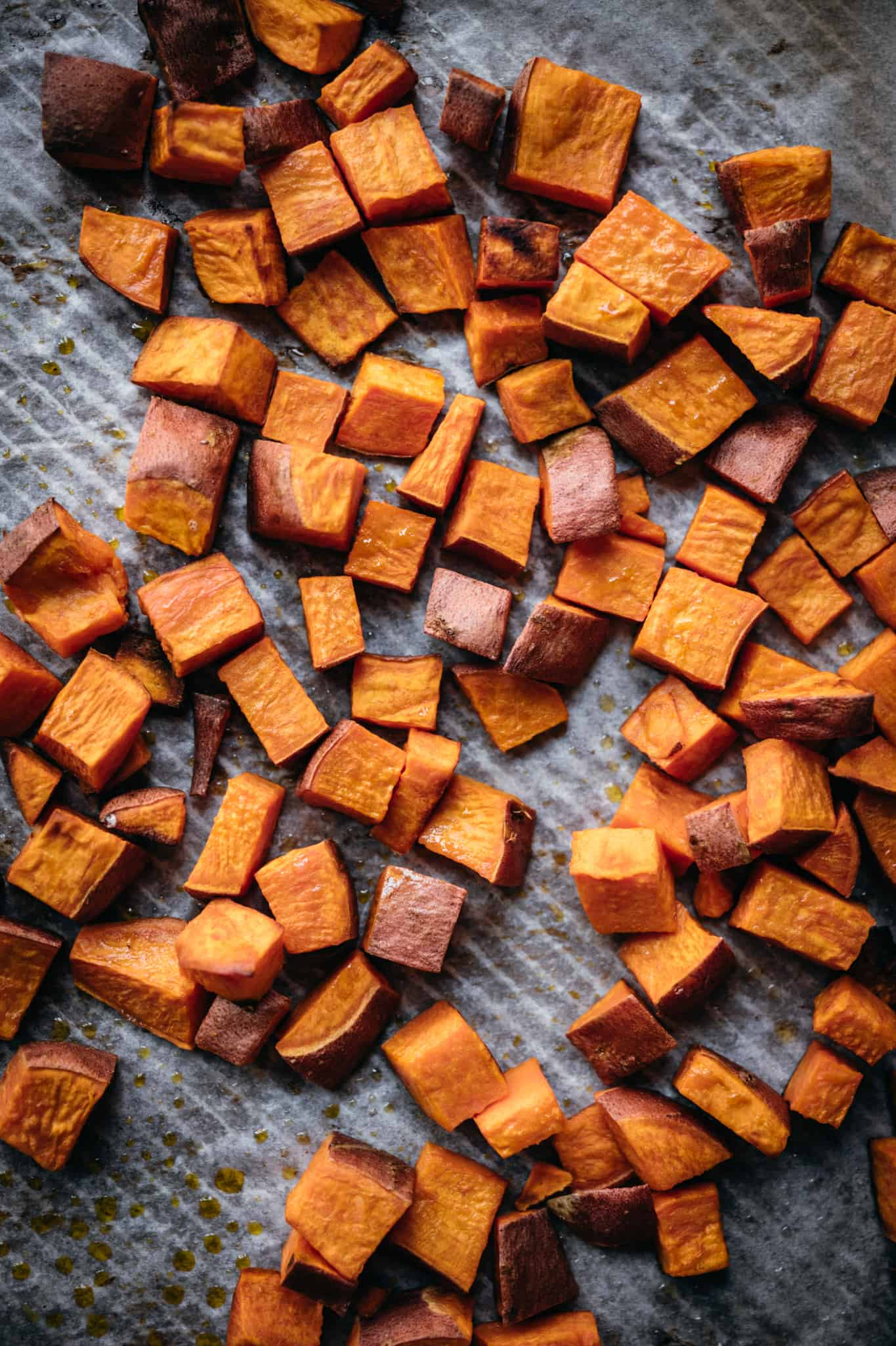 overhead view of roasted sweet potatoes on a sheet pan