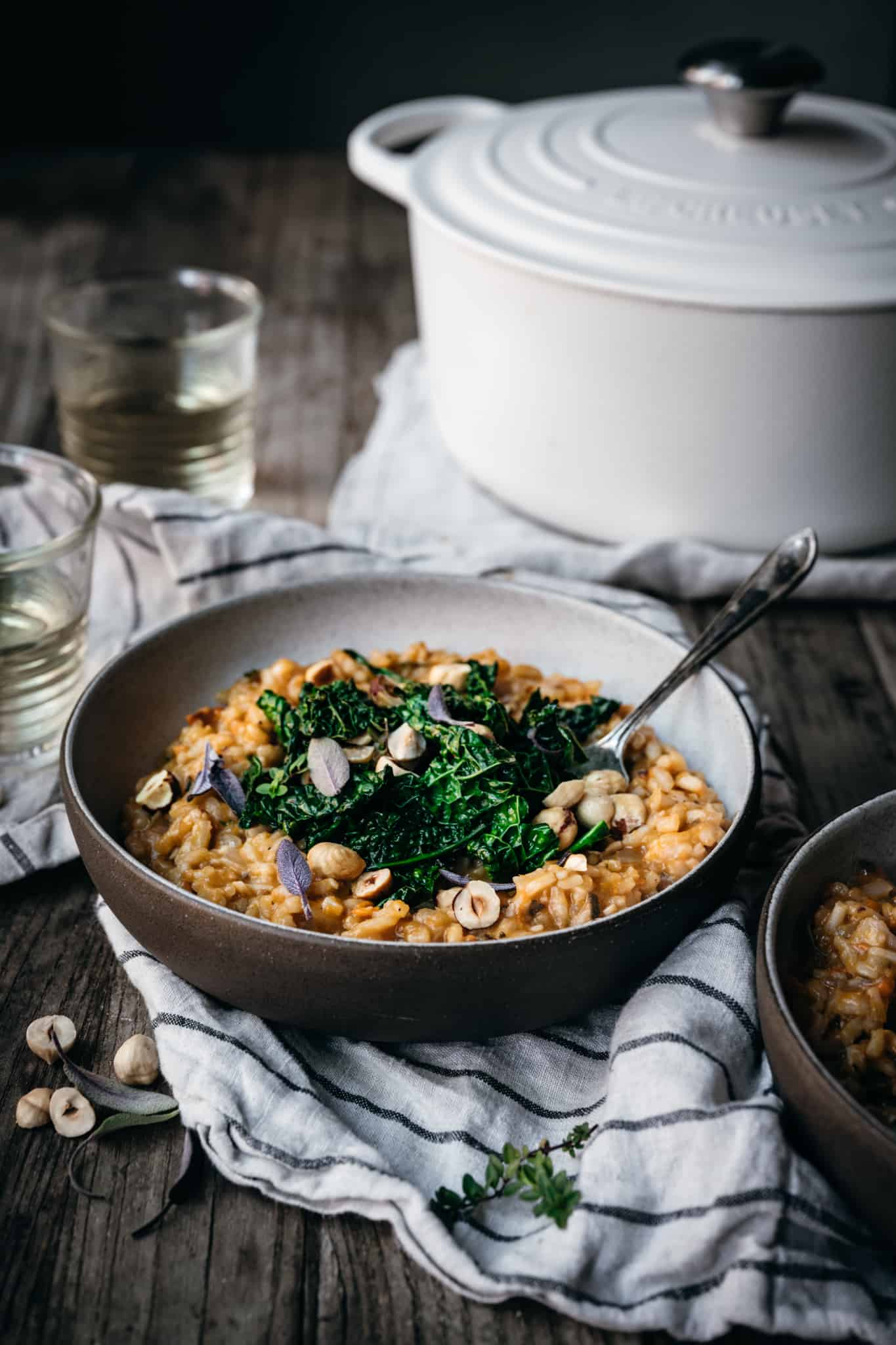 Side view of vegan sweet potato risotto topped with kale and hazelnuts