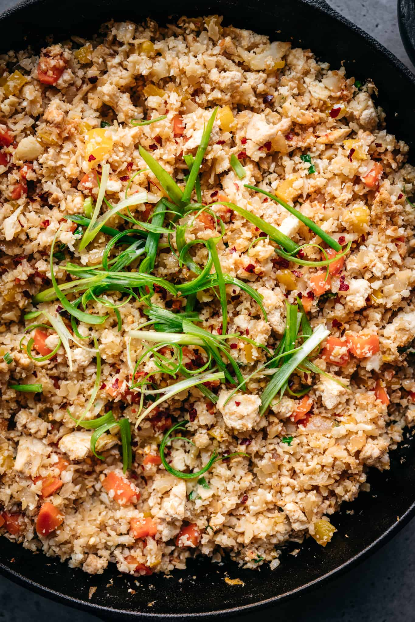close up overhead of vegan cauliflower fried rice in a cast iron skillet with scallions on top