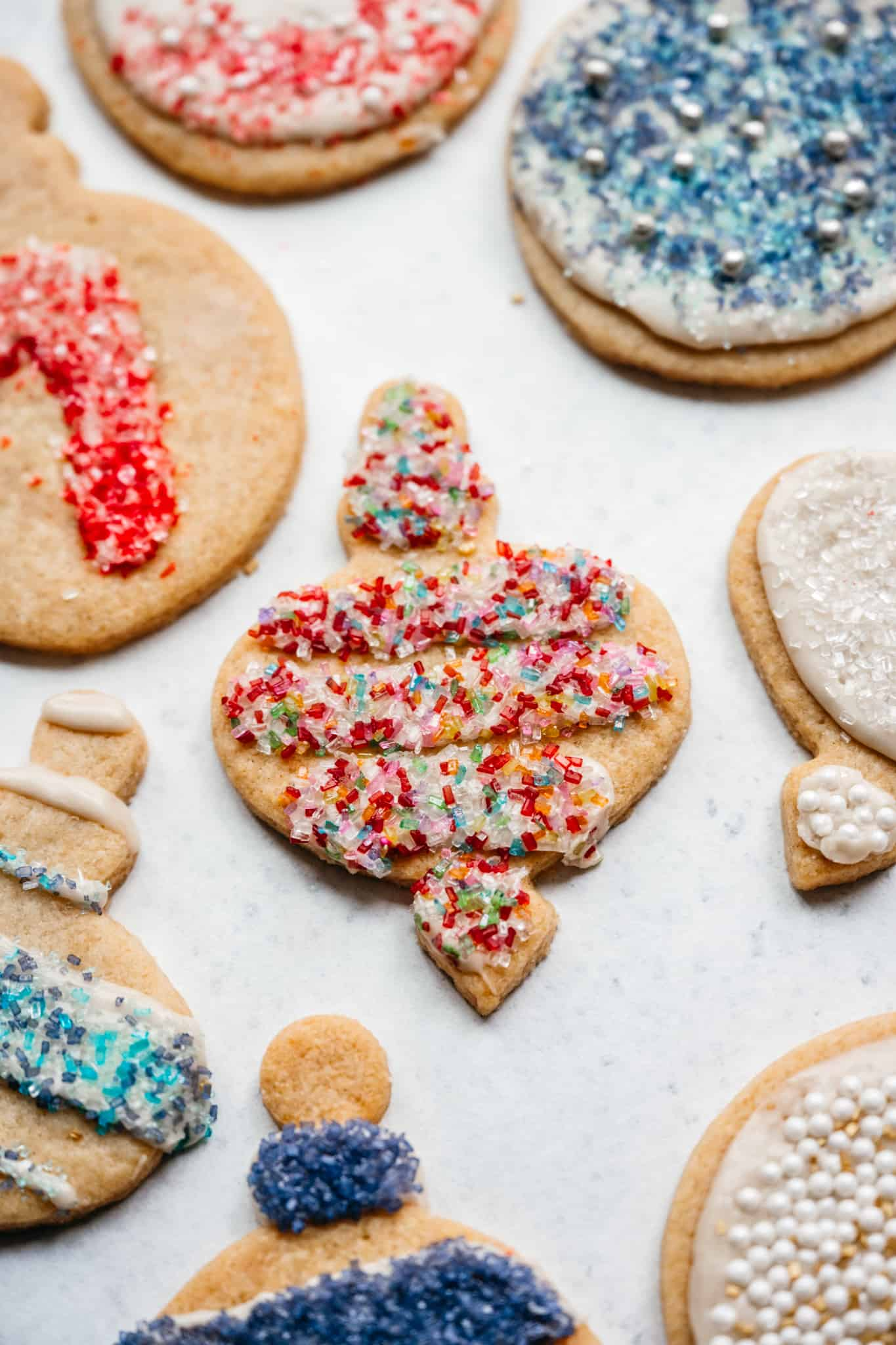 close up side view of vegan christmas sugar cookie in ornament shape with sprinkles