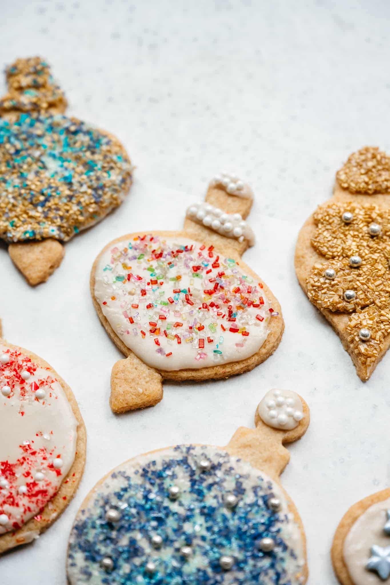 close up side view of vegan sugar cookies with icing and sprinkles