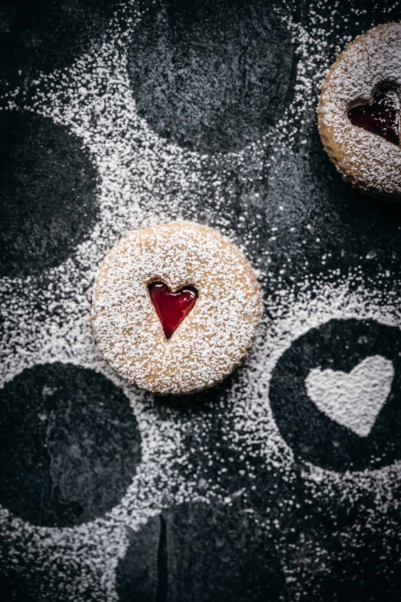 overhead view of linzer cookie with small heart cut out on black background with powdered sugar