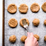 Peanut butter cookies receiving indents from a fork.