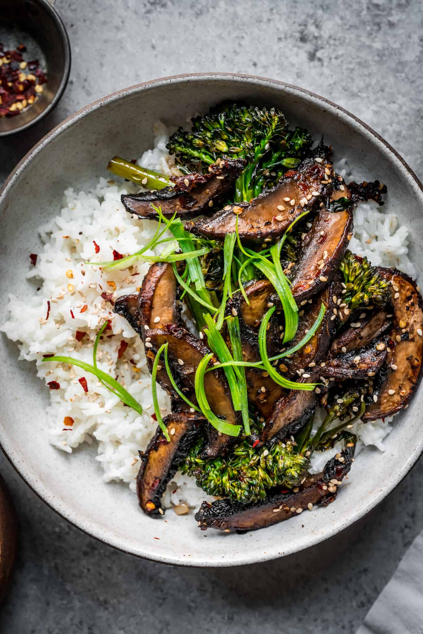 overhead of vegan teriyaki mushroom bowls with white rice and broccolini