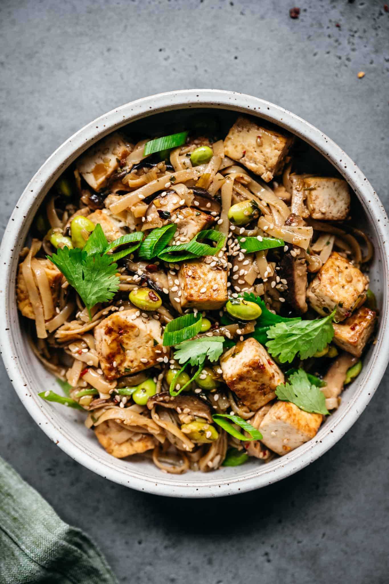 close up view of vegan rice noodles with crispy tofu, mushrooms and edamame in white bowl