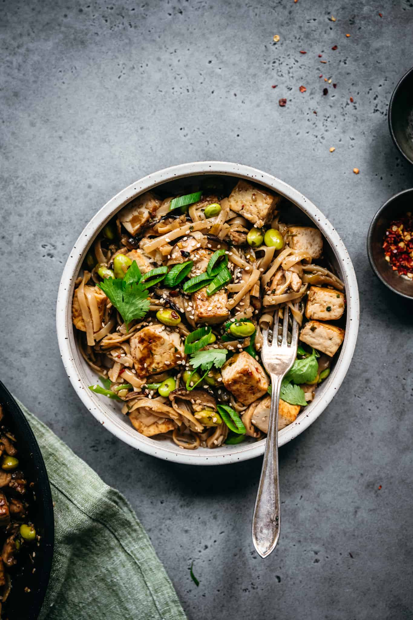 close up view of vegan rice noodles with crispy tofu, mushrooms and edamame in white bowl with fork