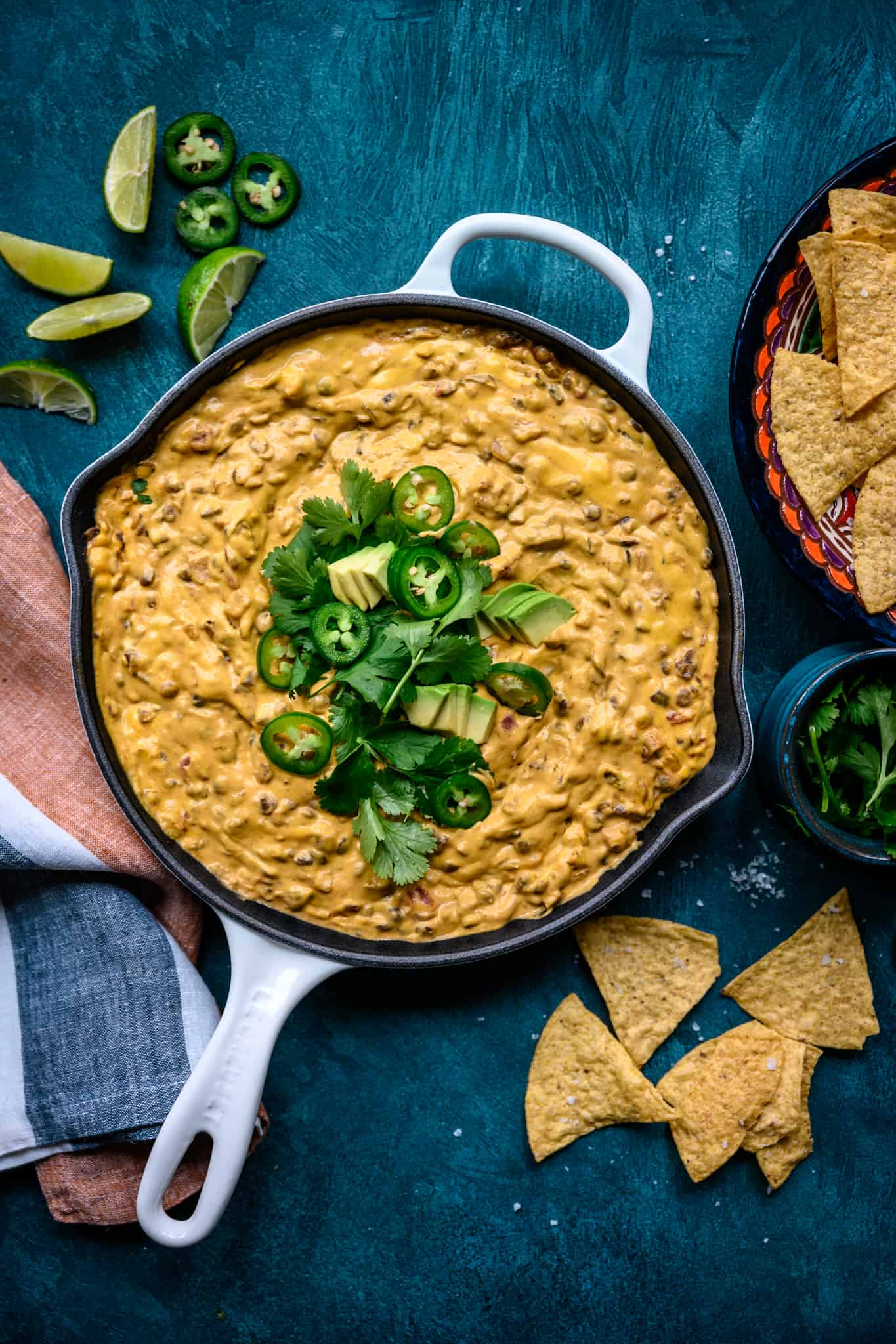overhead view of vegan chile con queso dip with tortilla chips in skillet on blue background