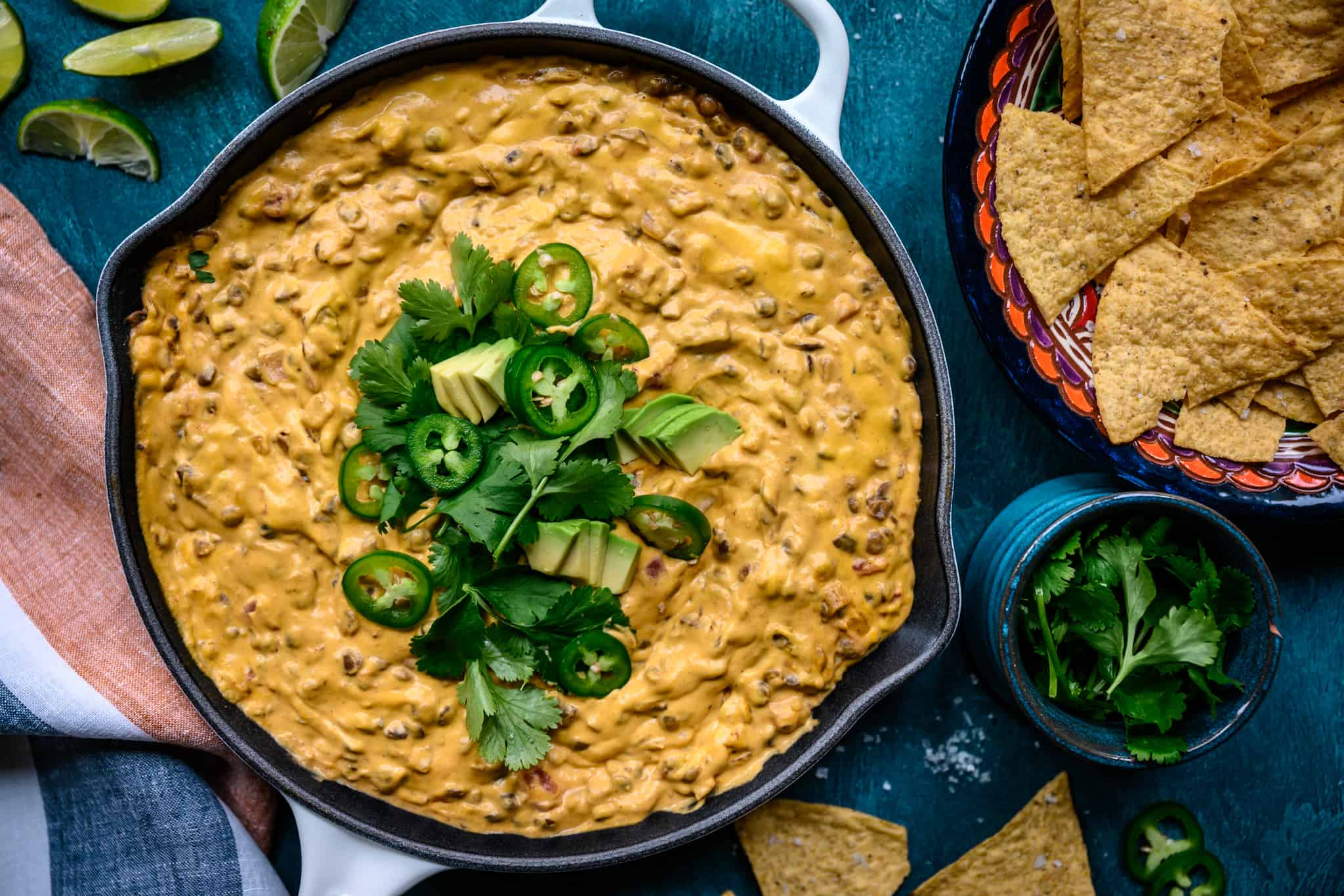 overhead view of vegan chile con queso dip in skillet with tortilla chips
