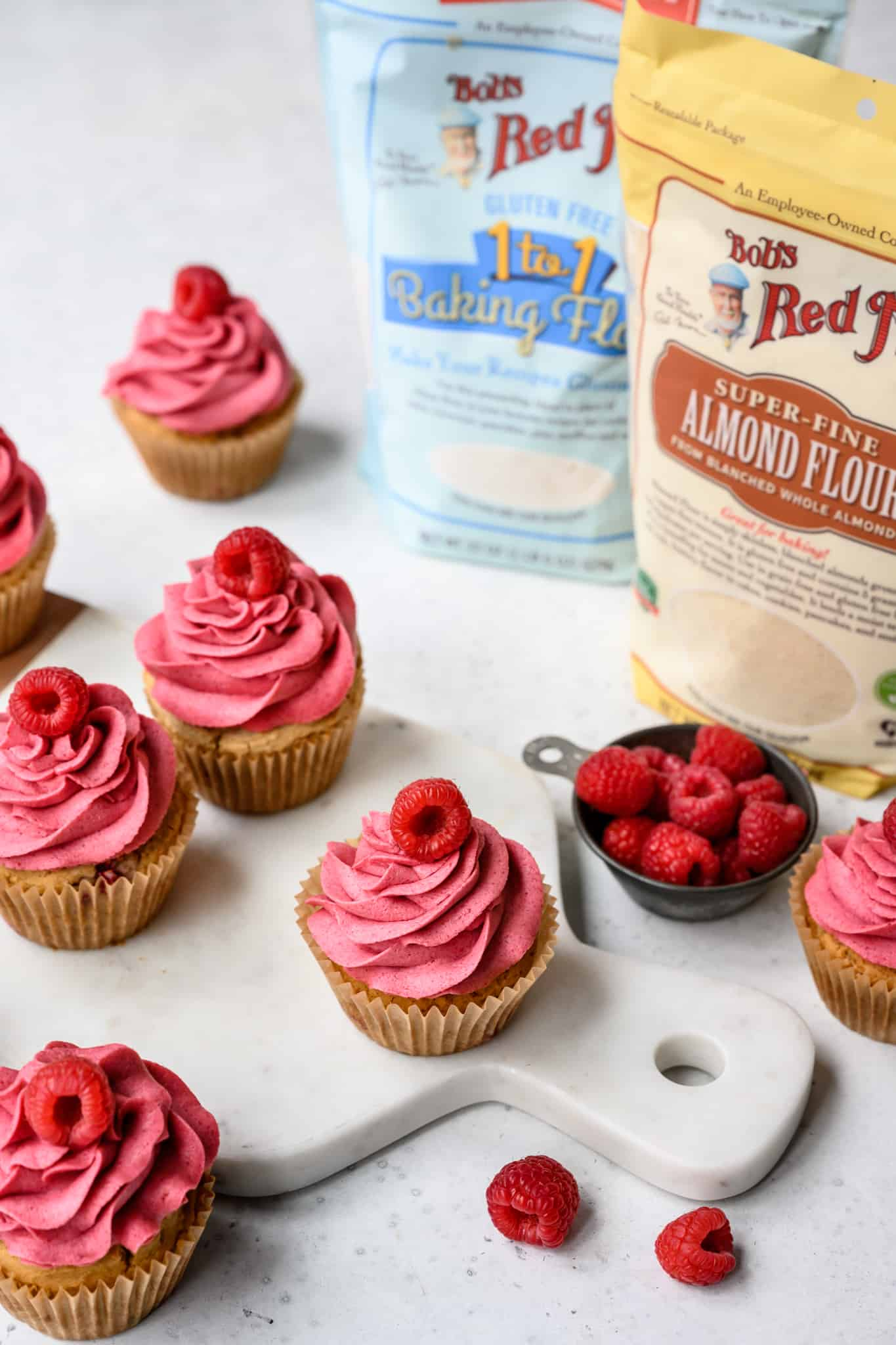 side view of raspberry almond cupcakes on white background with Bob's Red Mill products
