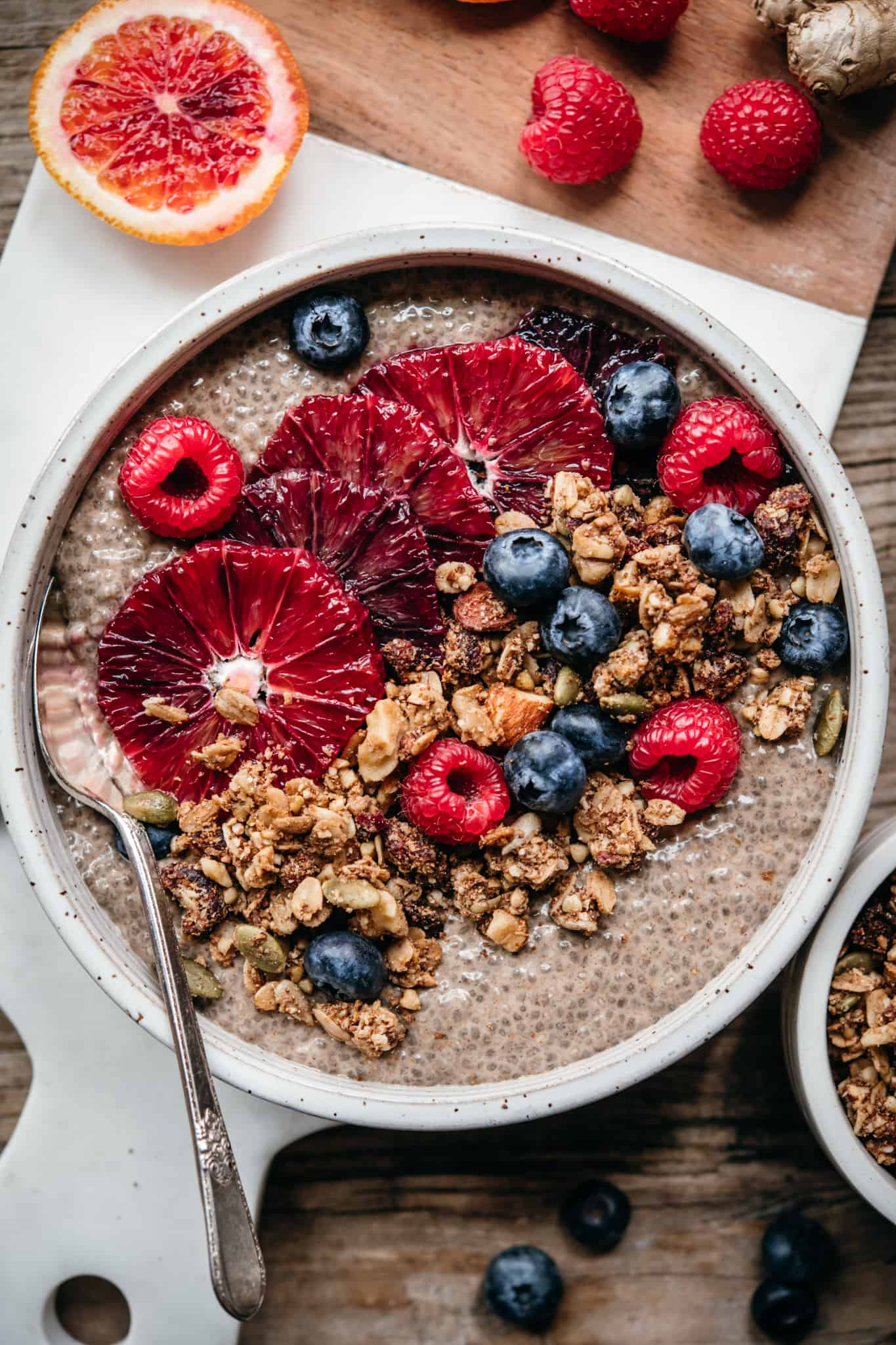 close up overhead view of chai chia pudding in white ceramic bowl with berries and granola