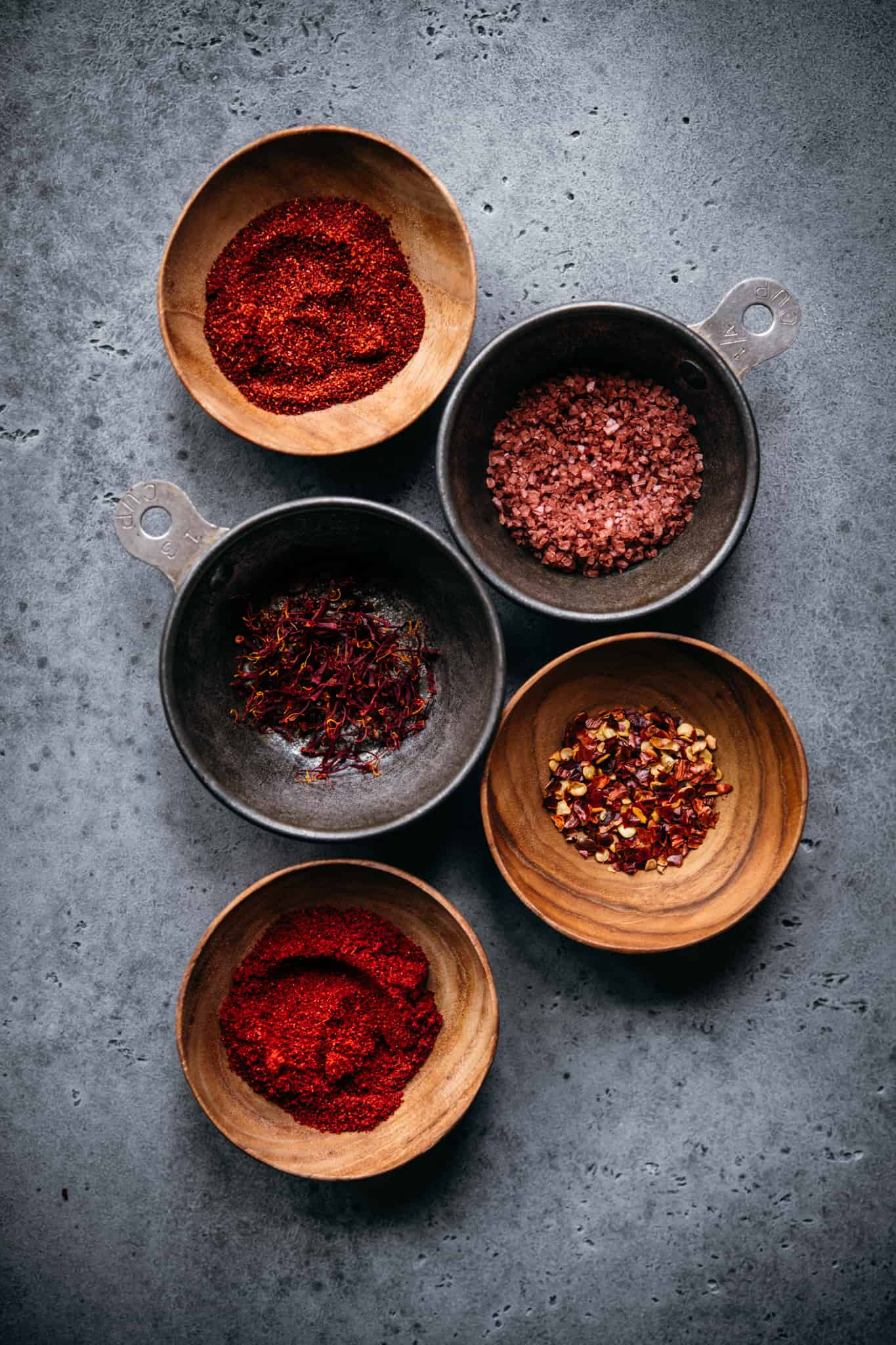 overhead view of spices in small bowls to use in vegan paella recipe