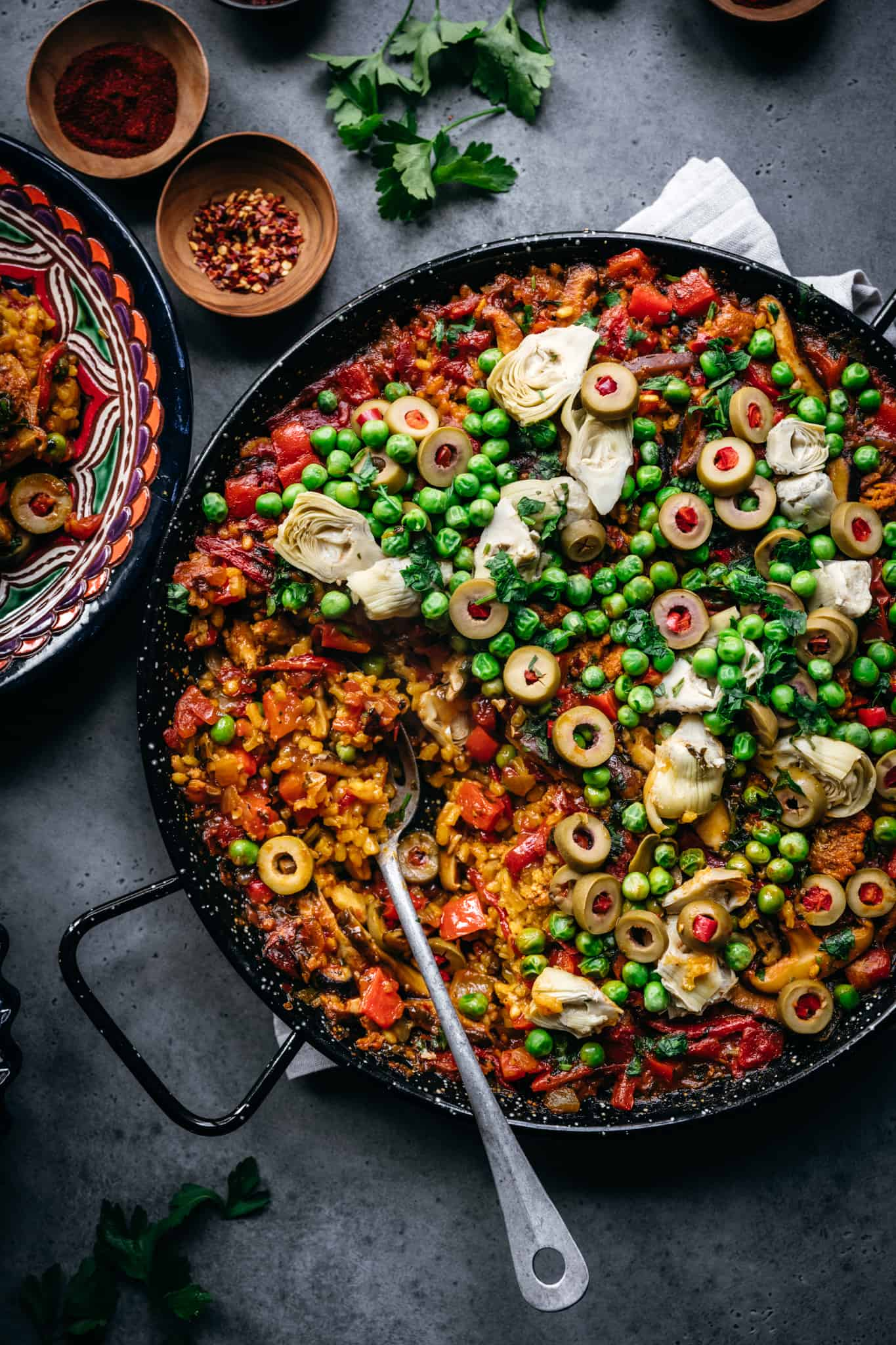 overhead view of vegan paella with peas, vegan chorizo, artichokes and olives