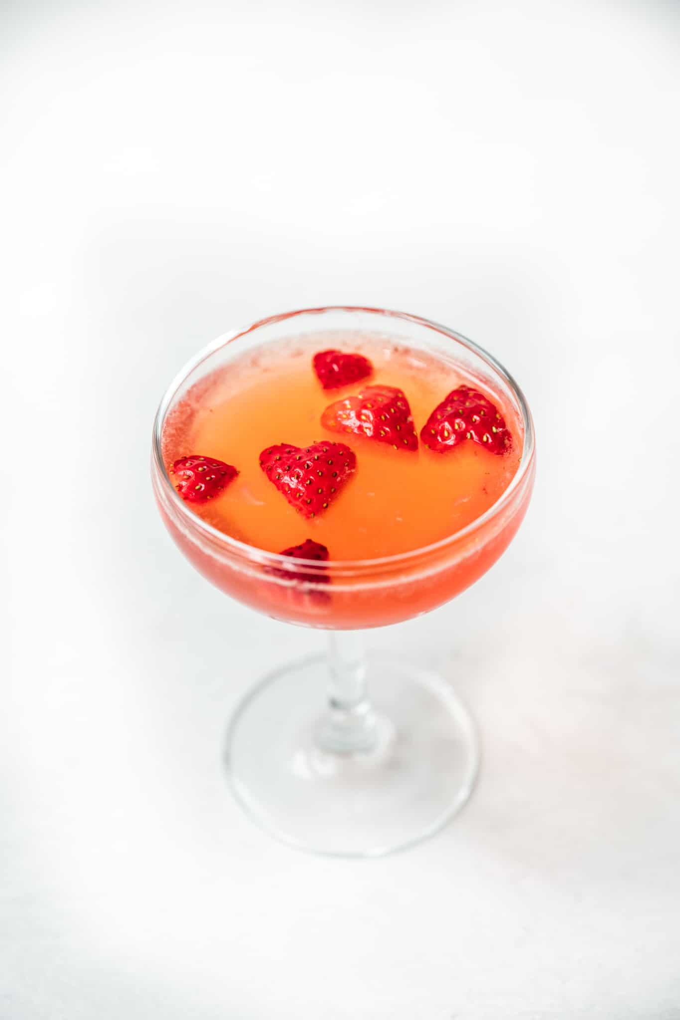 side view of valentine's day cocktail garnished with strawberry hearts
