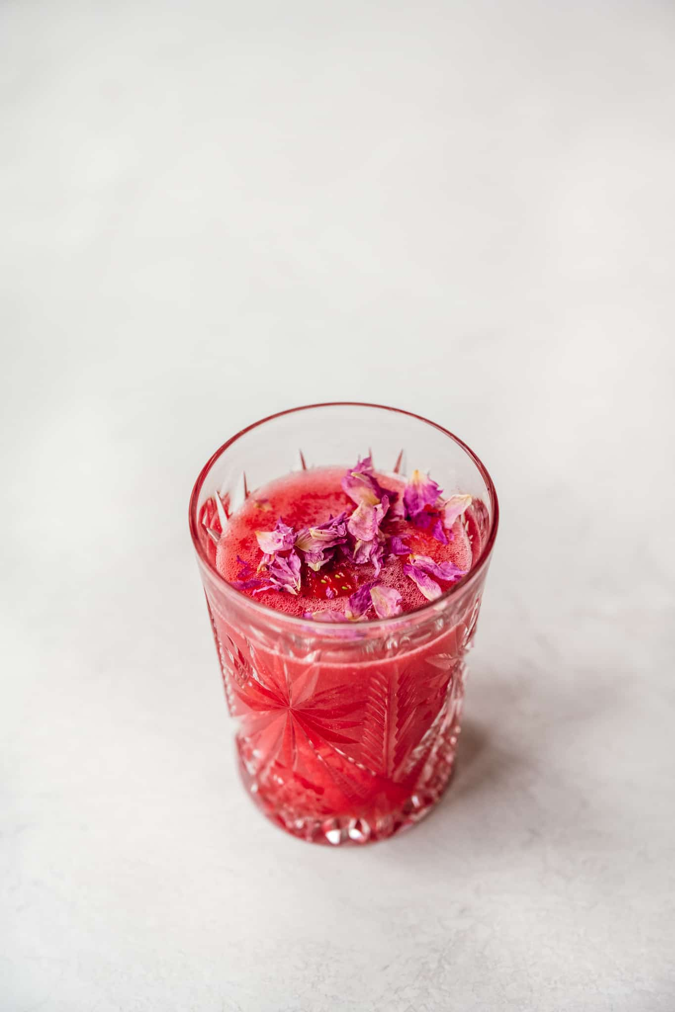 side view of nonalcoholic valentine's day mocktail in antique cocktail glass