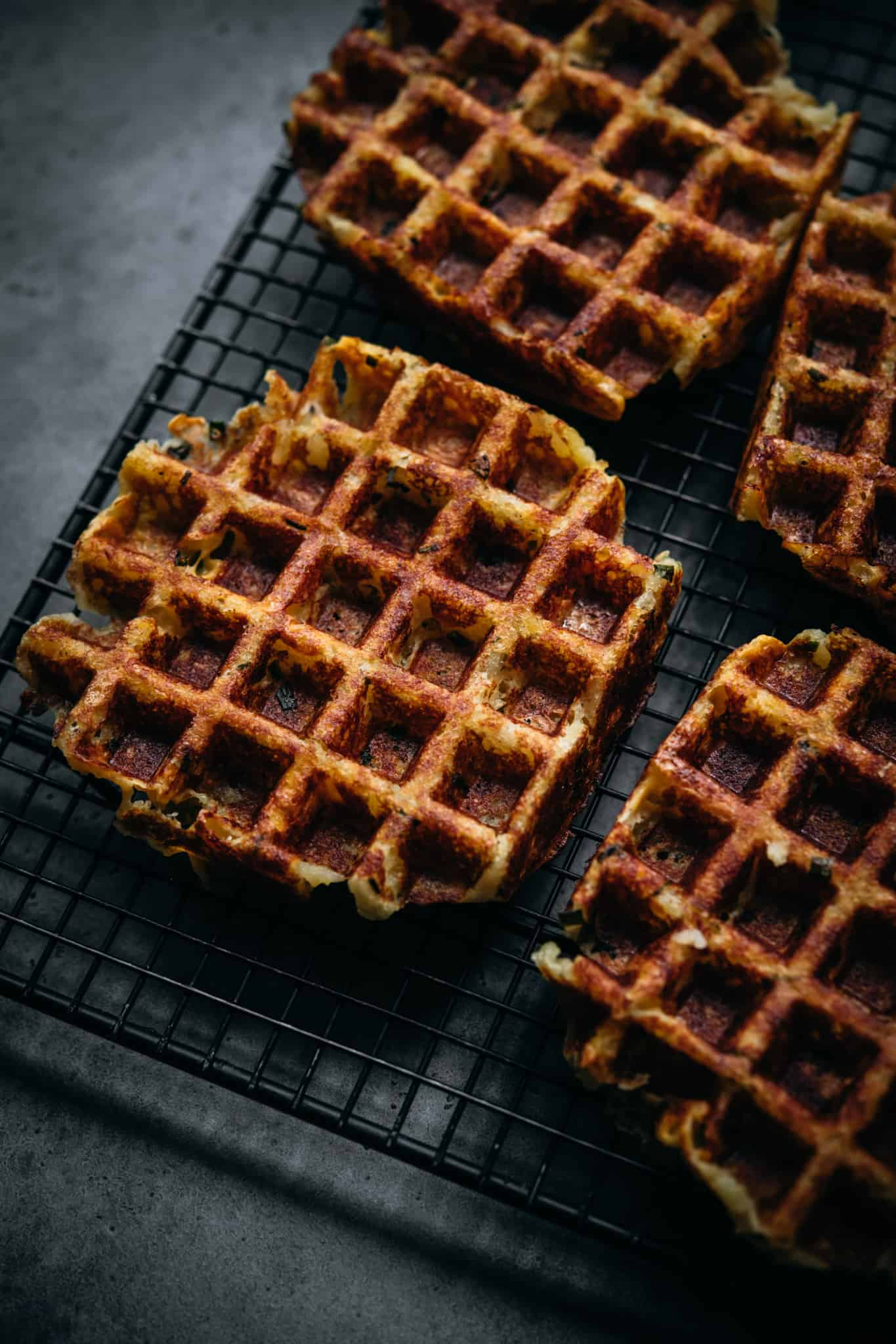 side view of crispy mashed potato waffles on cooling rack