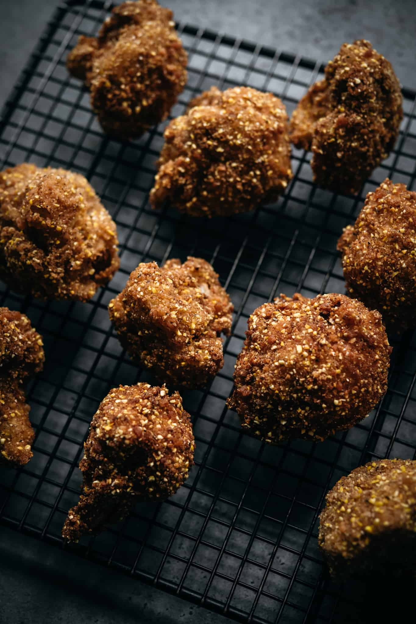 side view of vegan fried cauliflower bites on cooling rack