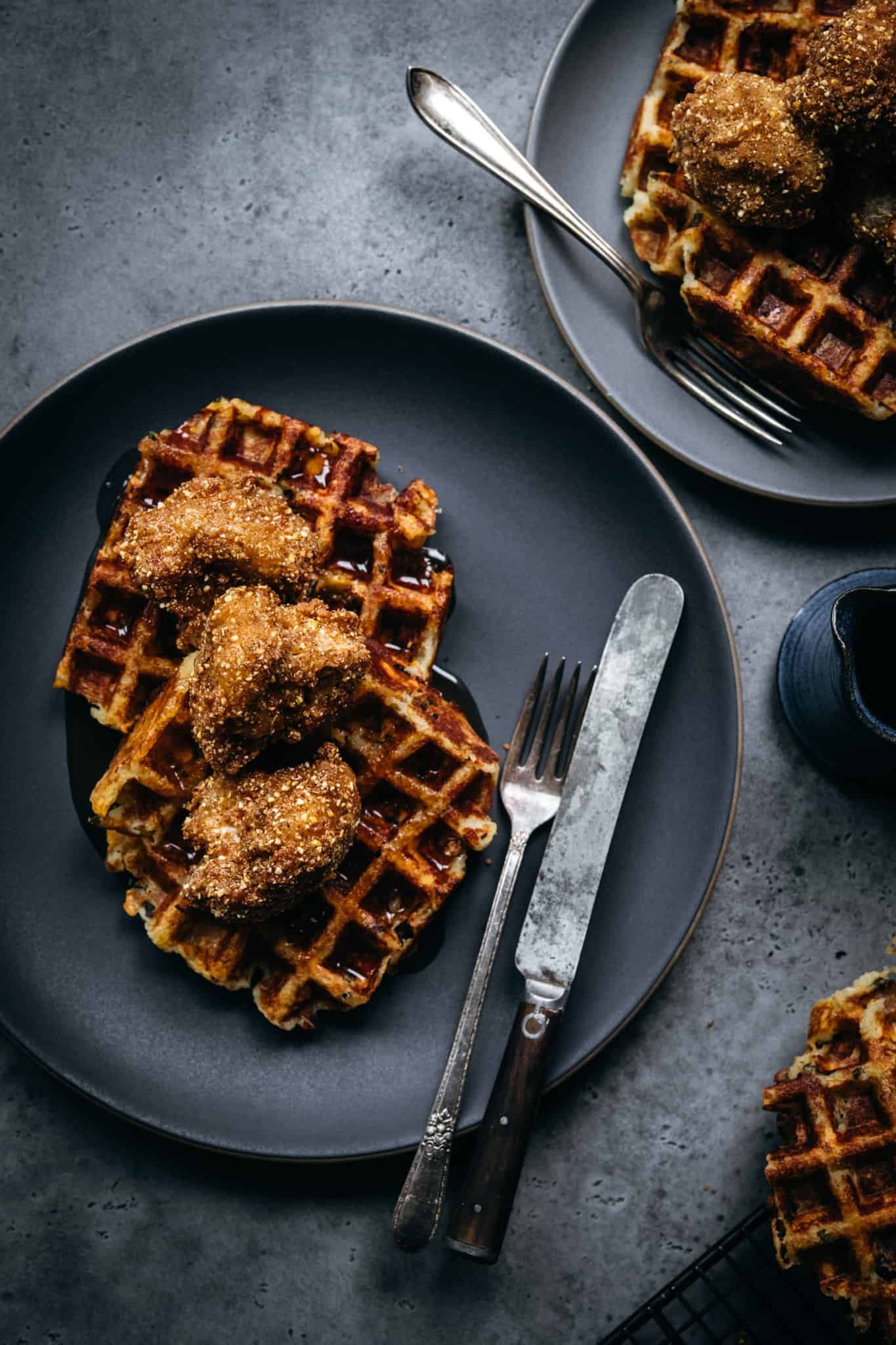 overhead view of vegan chicken and waffles on grey plate with hot maple syrup and fork