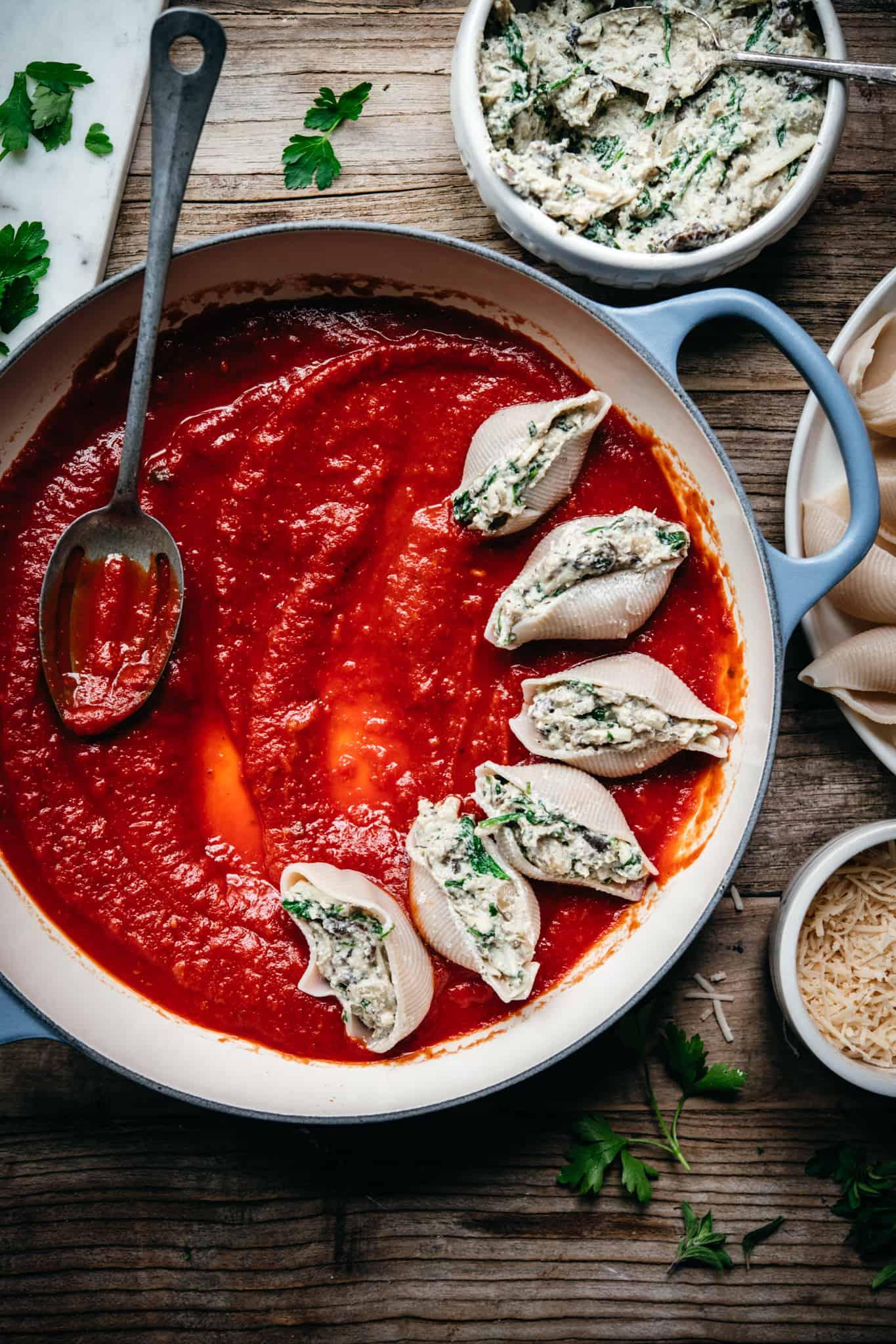adding stuffed shells to circular pan with marinara sauce