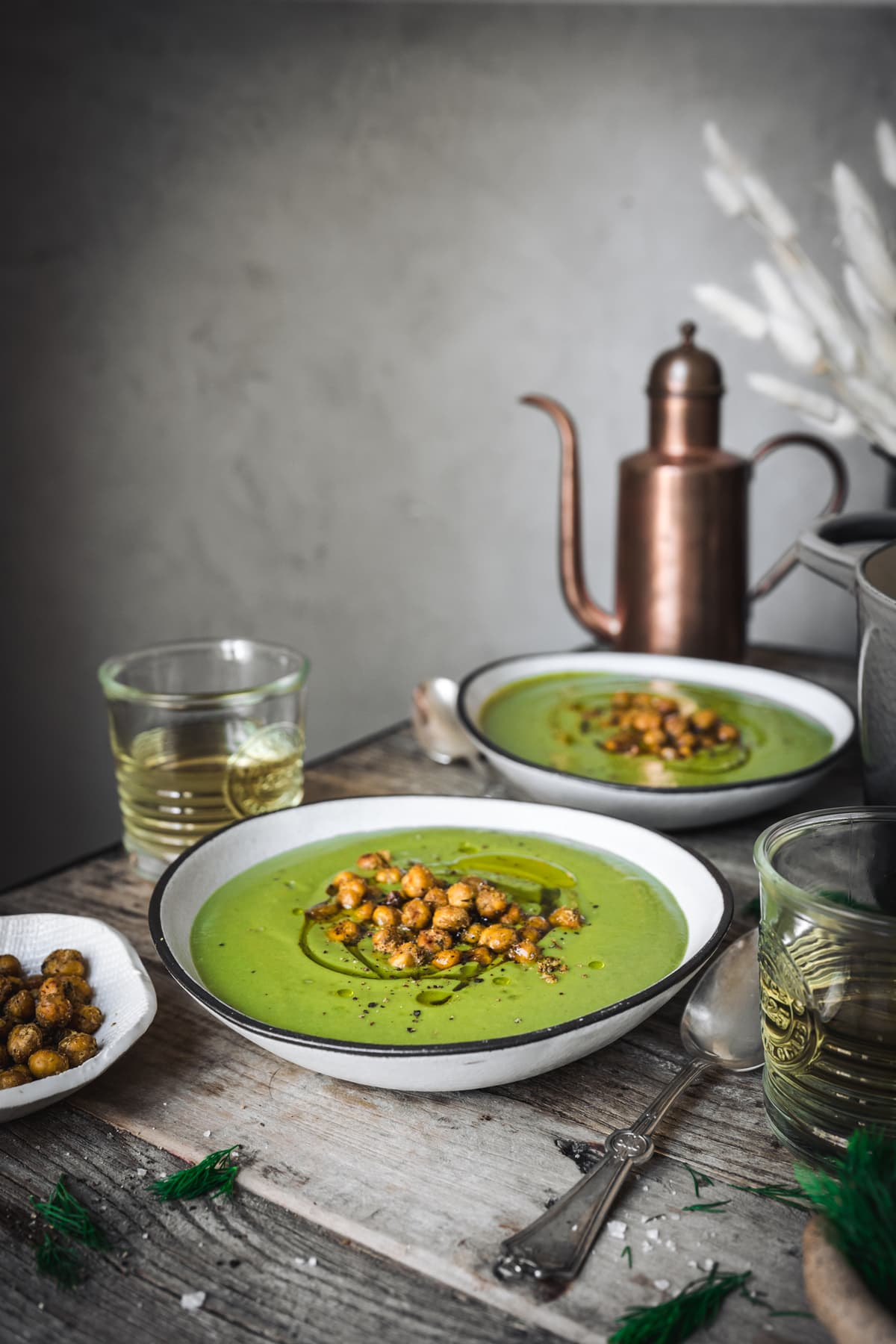side view of vegan broccoli potato soup in a white bowl on wood table