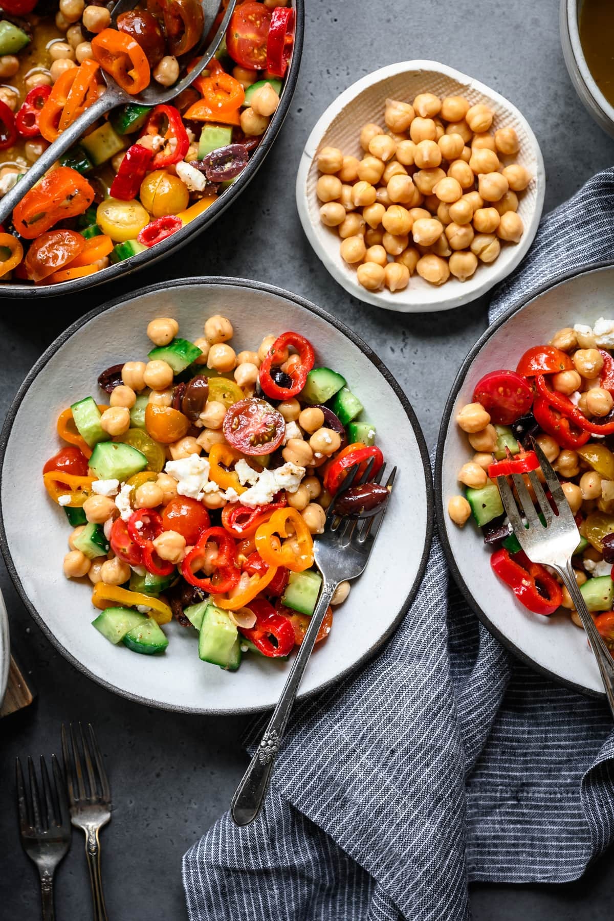 overhead view of greek chickpea salad in bowls with forks