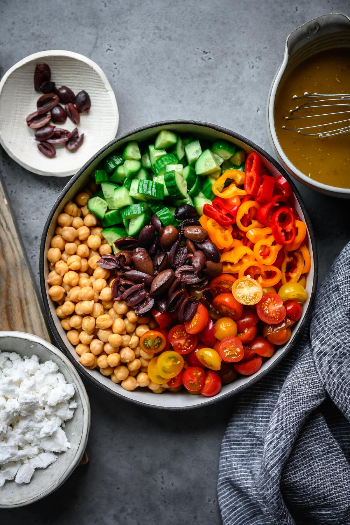 overhead view of greek chickpea salad ingredients in mixing bowl