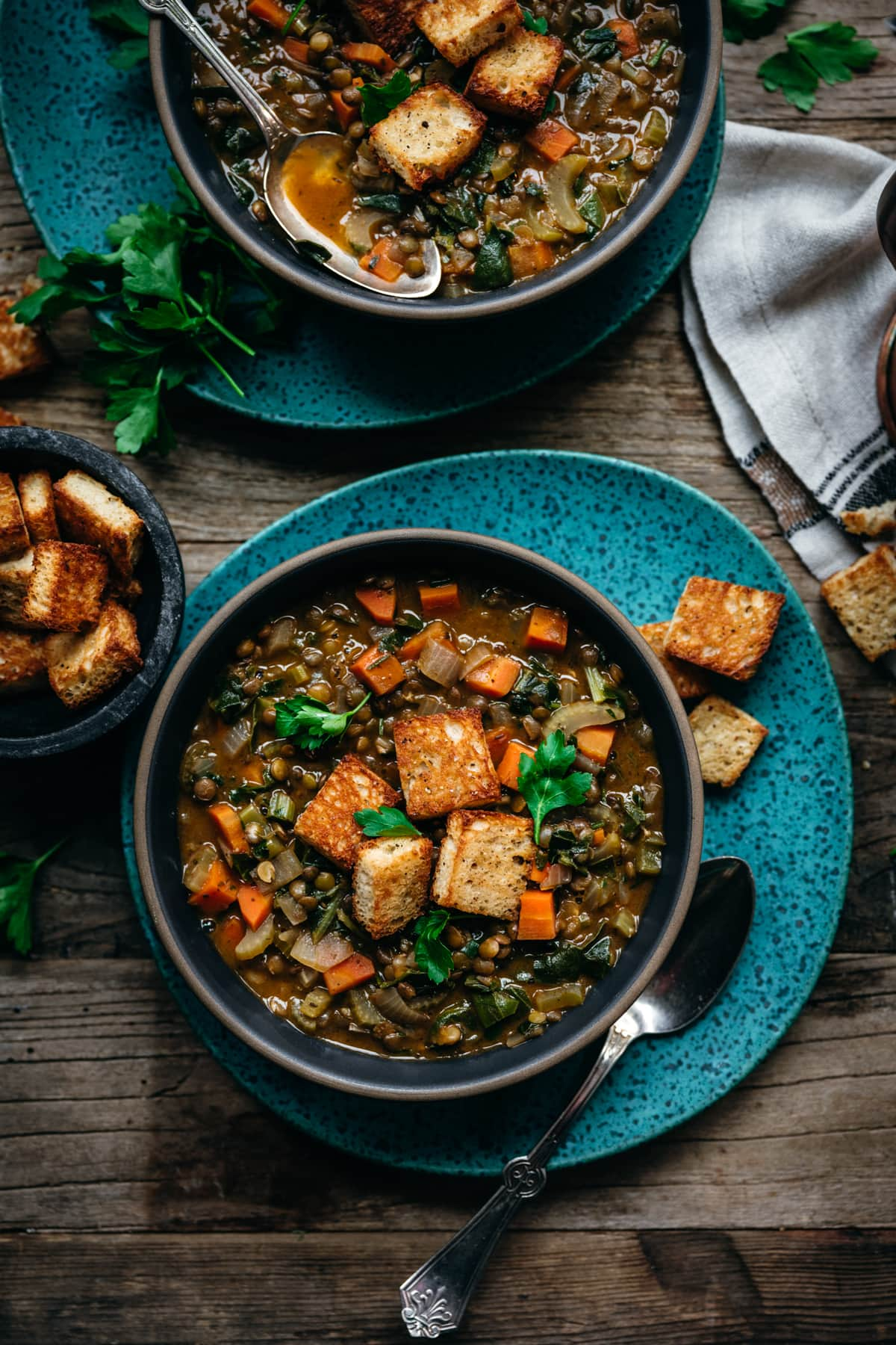 overhead view of vegan lentil stew topped with garlicky croutons
