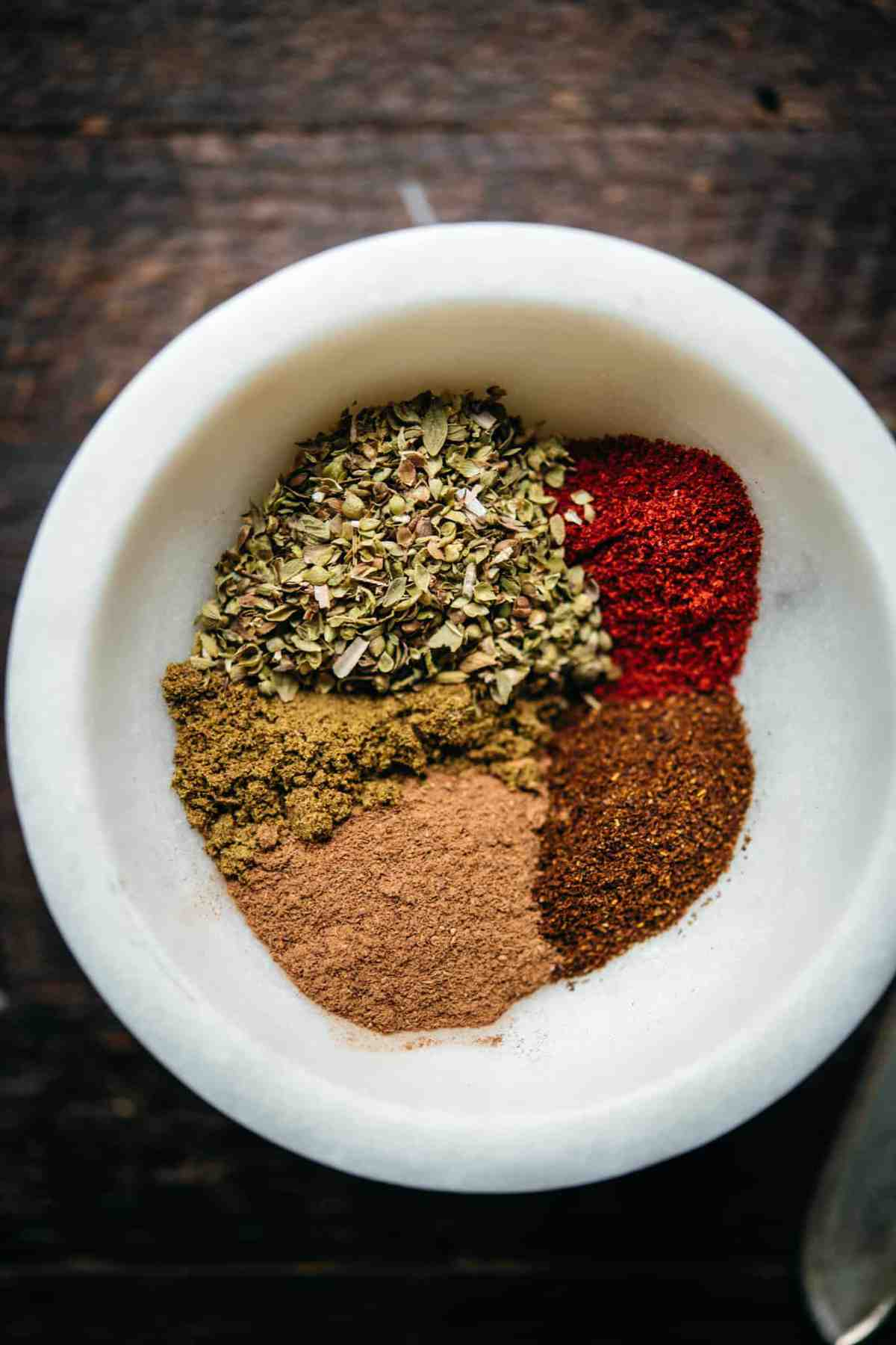 overhead view of spices for vegan chili in a small bowl