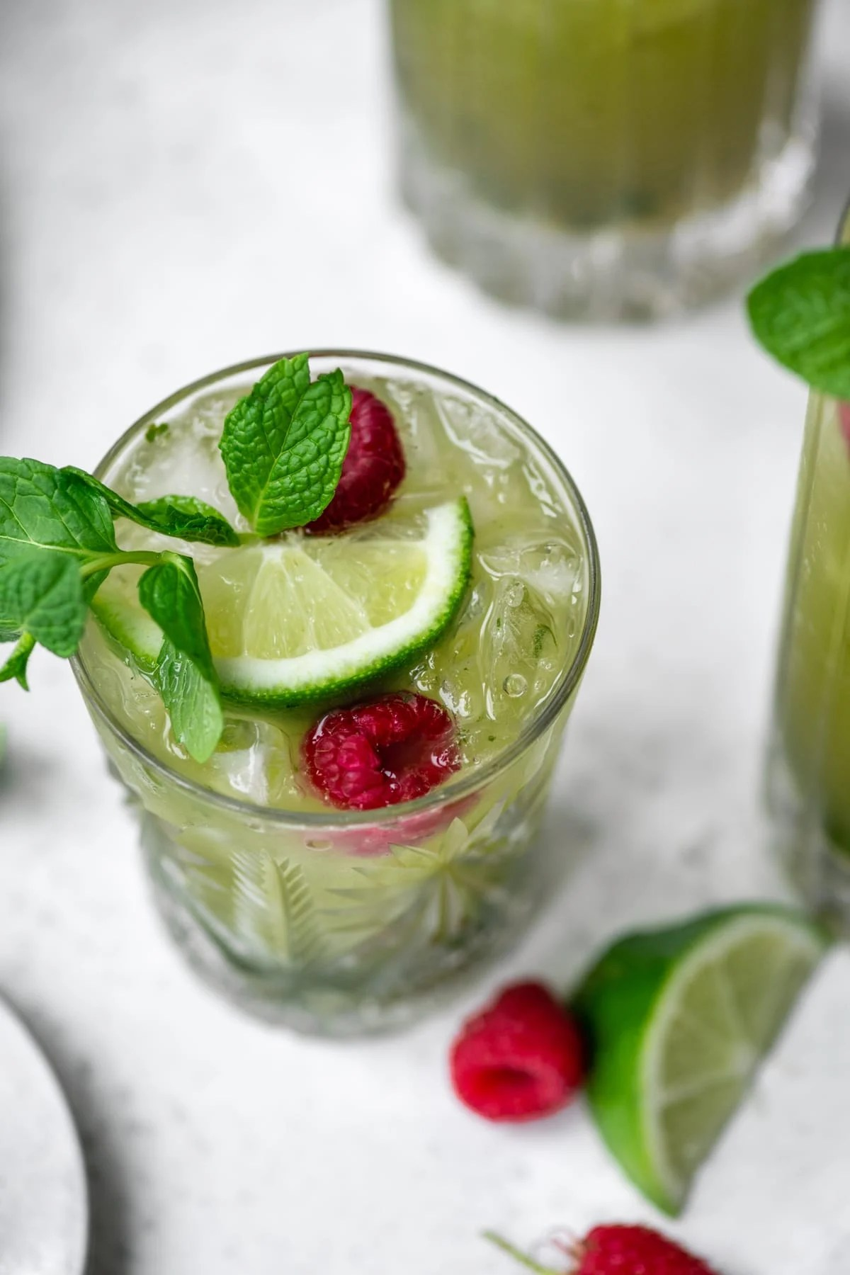 close up view of nonalcoholic matcha drink in glass with lime and mint