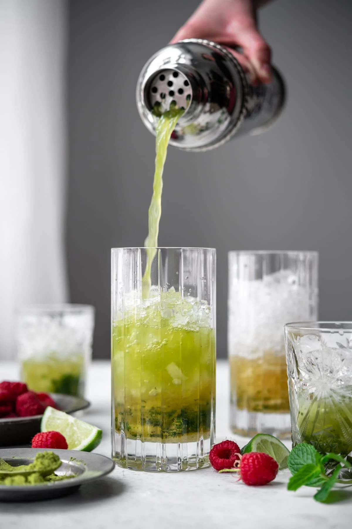 side view of pouring matcha mojito into highball glass from cocktail shaker