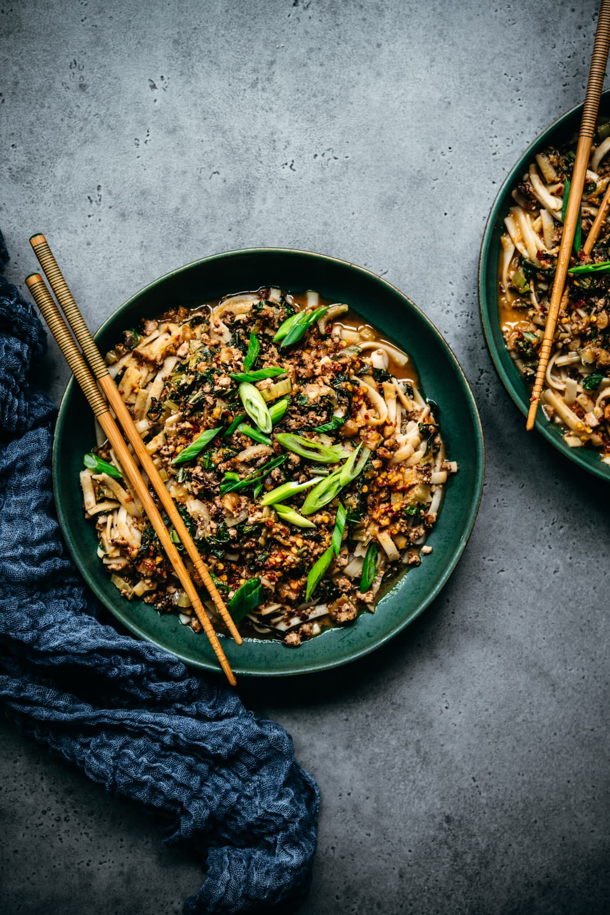 overhead view of vegan dan dan noodles with scallions and chopsticks in blue bowl