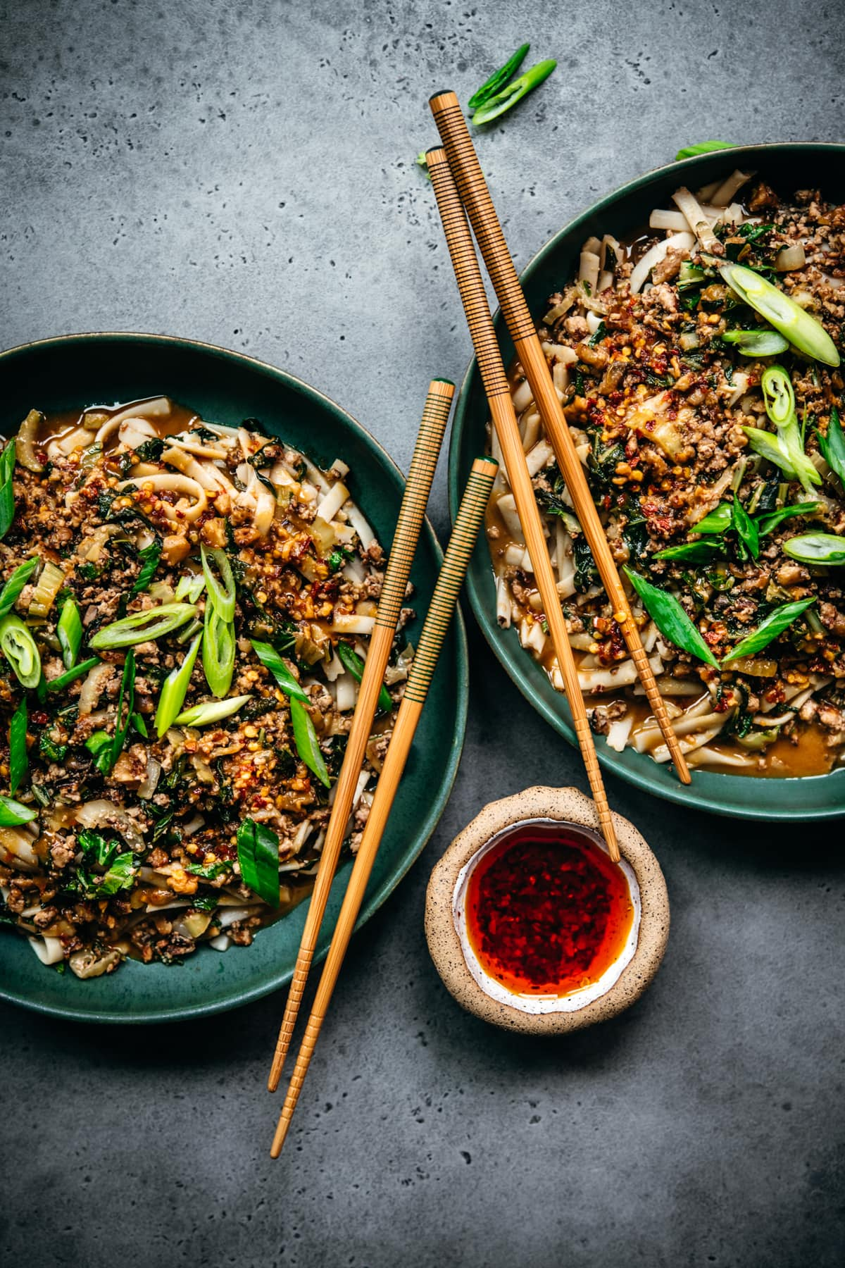 overhead view of two bowls of vegan dan dan noodles with chili oil and chopsticks
