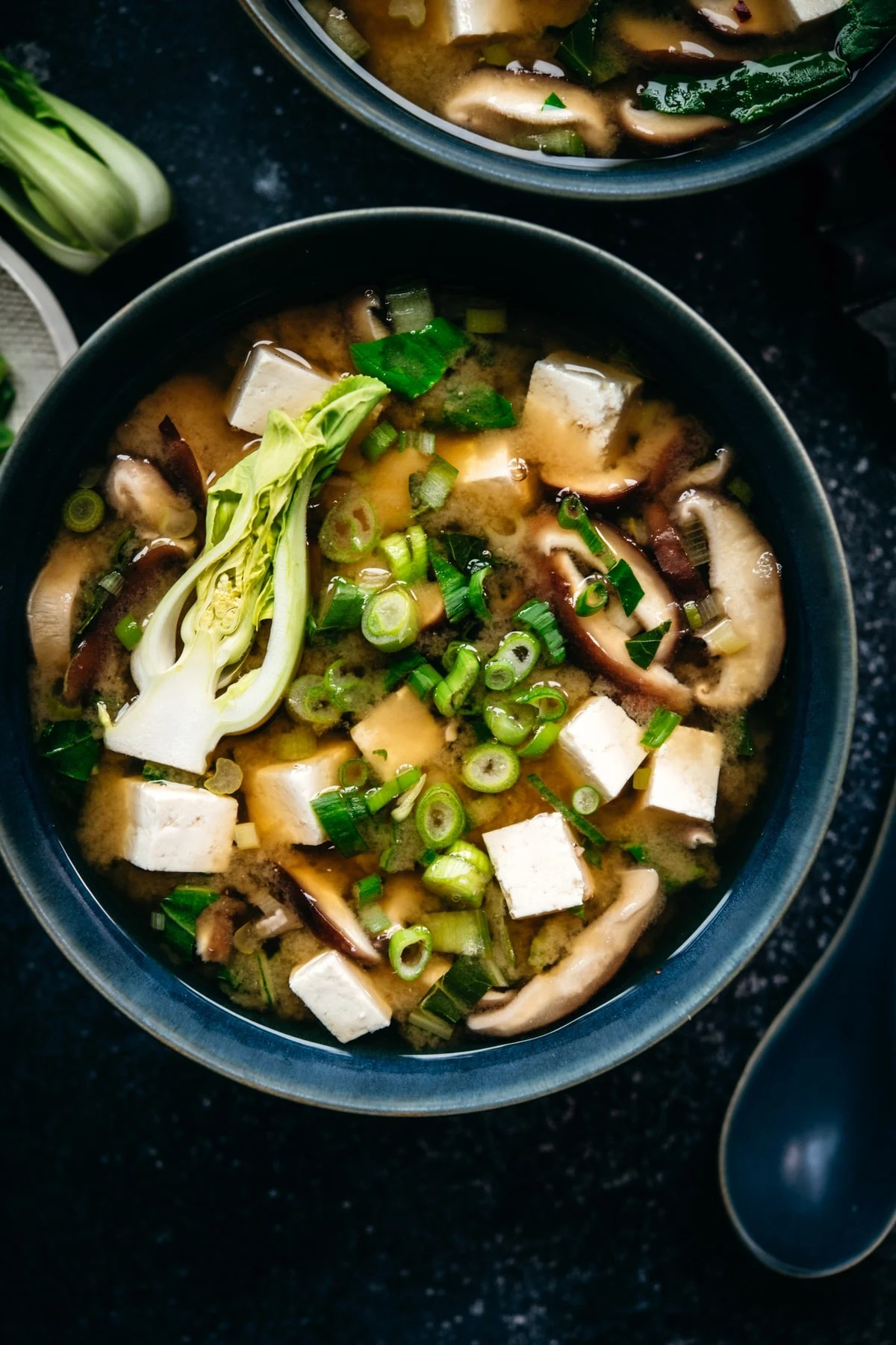 close up overhead view of vegan miso soup with tofu, mushrooms and scallions in a bowl