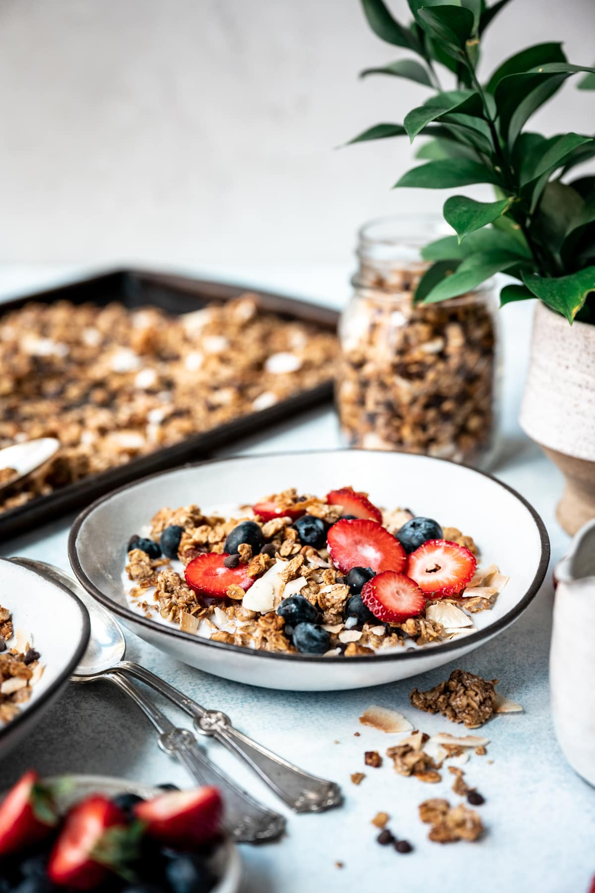 side view of banana bread granola in bowl with milk, strawberries and blueberries