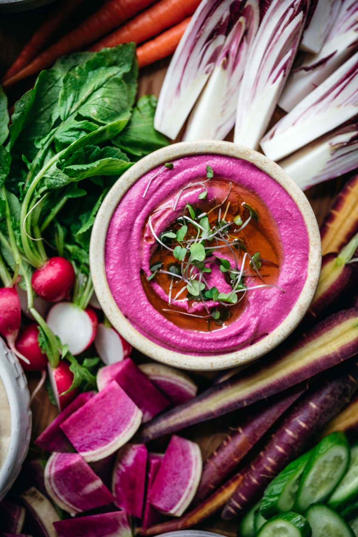overhead view of pickled beet hummus in a bowl with colorful fresh vegetables