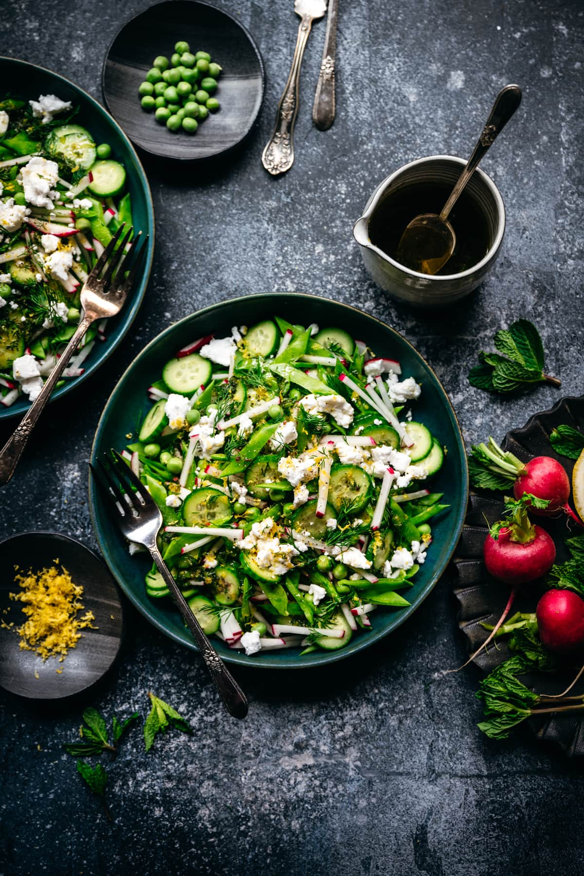 Overhead view of snow pea salad with radishes, cucumber and vegan feta in blue bowl