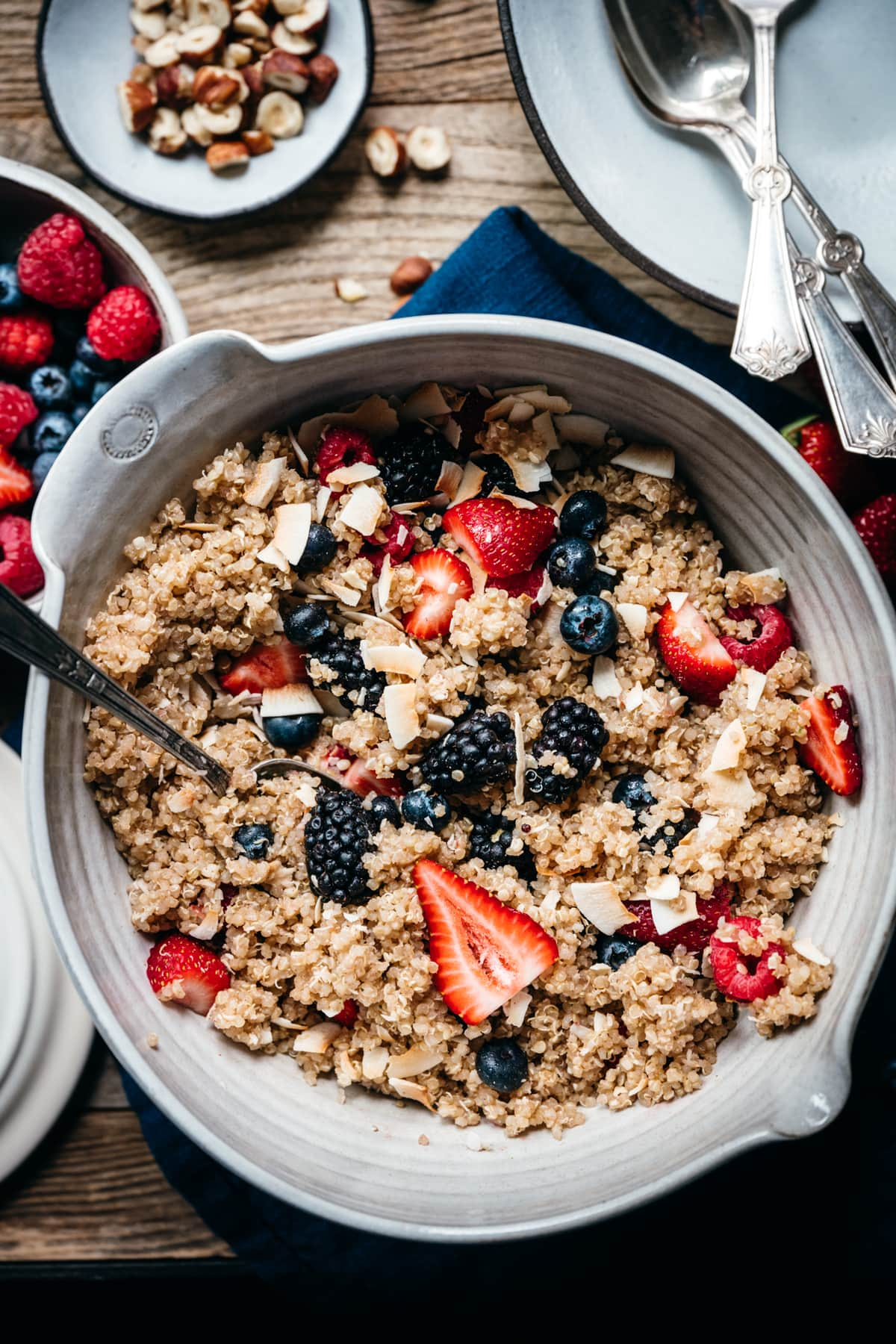overhead view of vegan breakfast quinoa with berries and coconut in a large mixing bowl
