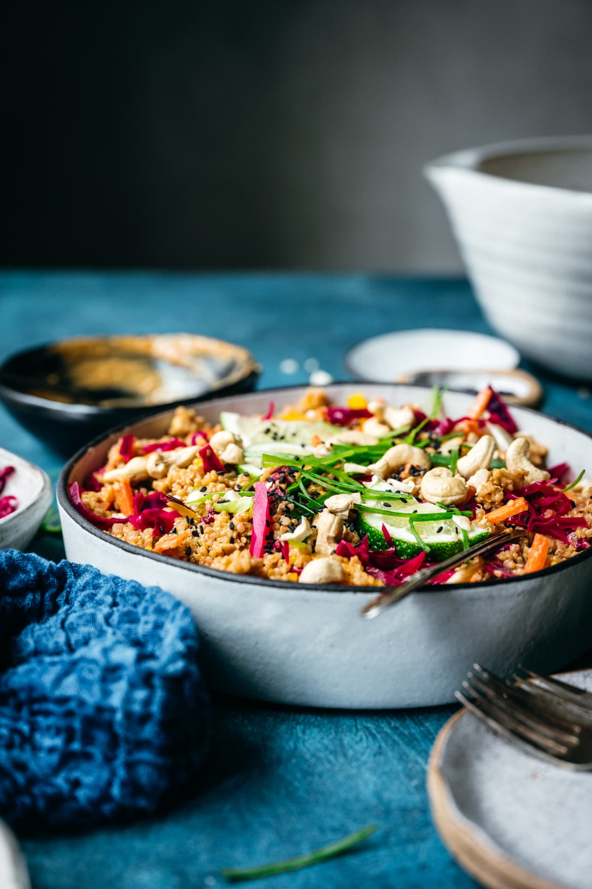 side view of vegan thai quinoa peanut salad in a white bowl